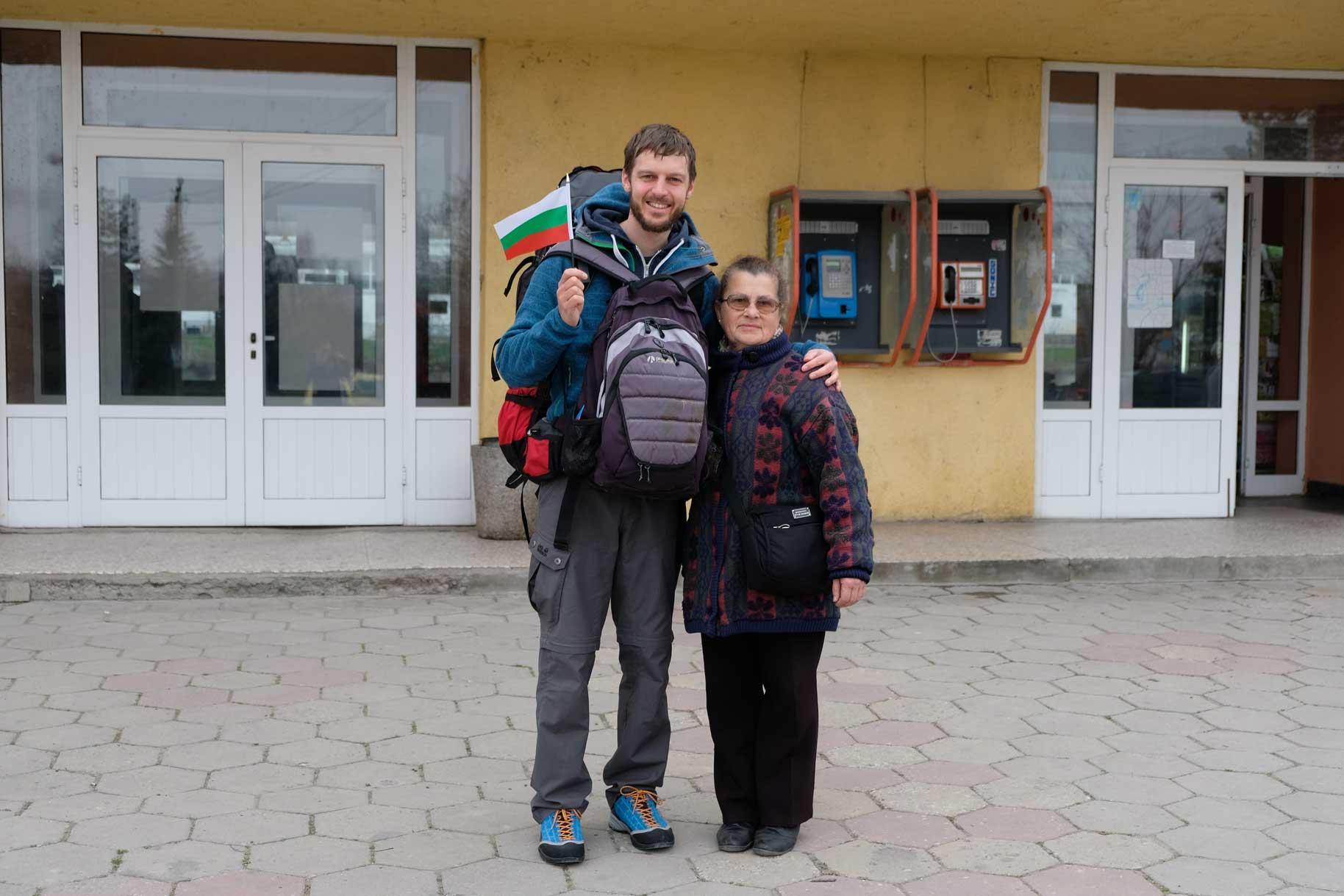 Sebastian steht mit Gepäck neben Petranka und hält eine Bulgarienfahne