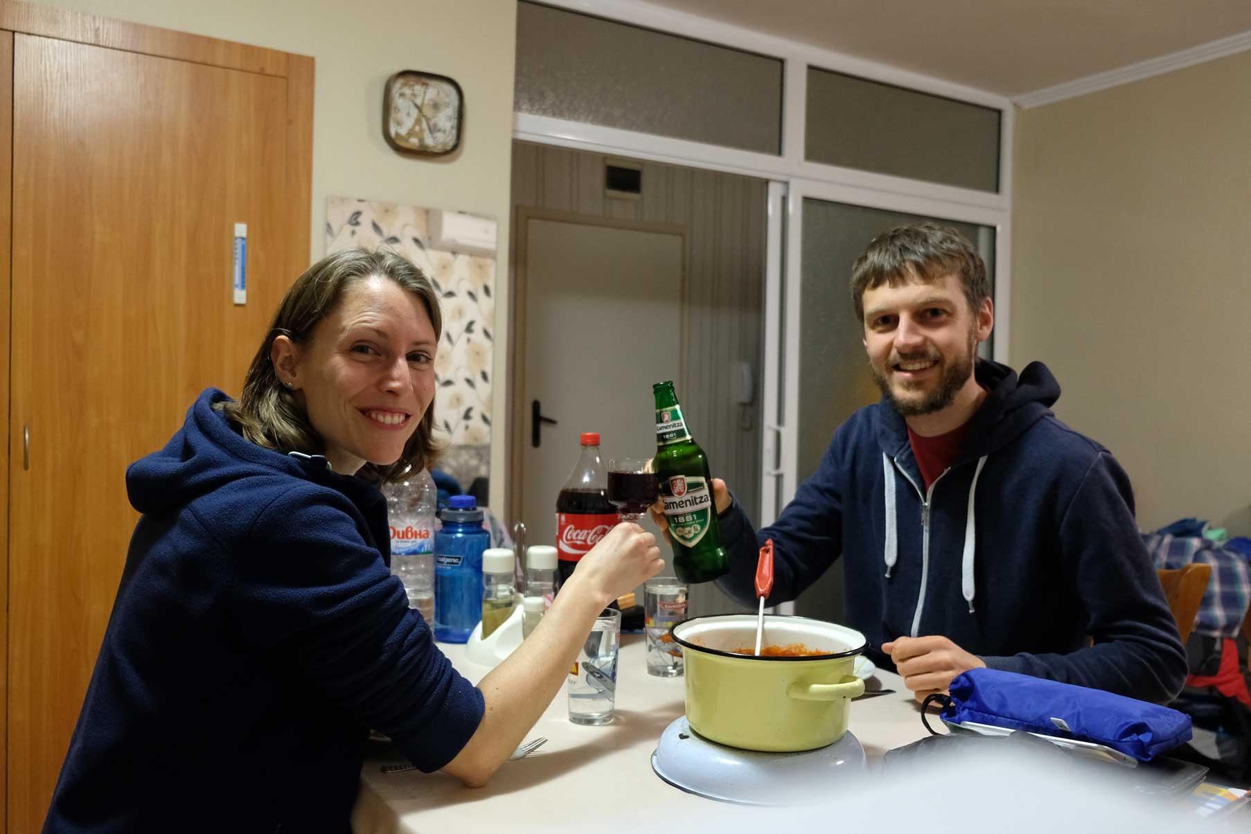 Leo und Sebastian sitzen am Tisch und stoßen mit Wein und Bier an