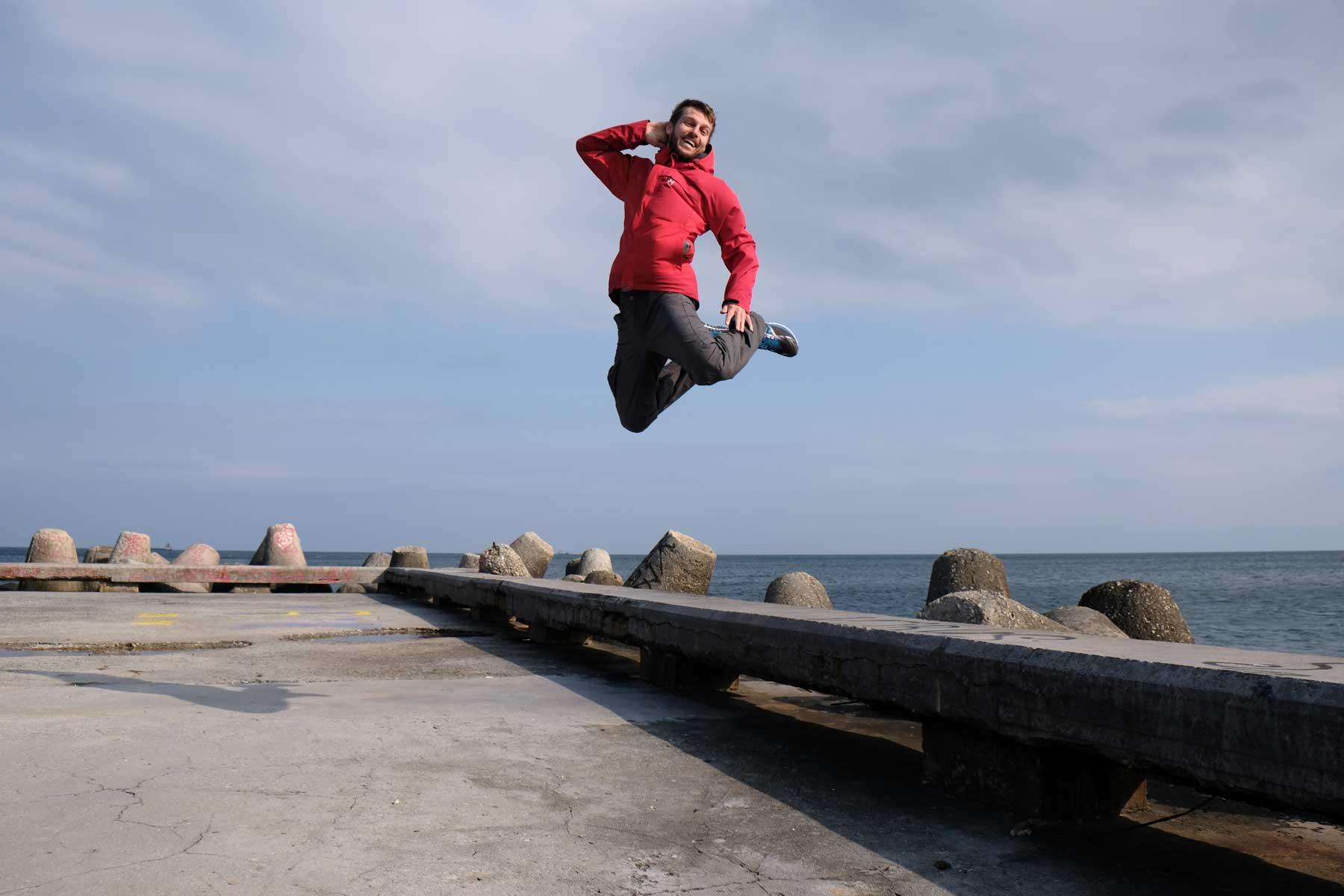 Sebastian springt von einer Steinbank am Meer