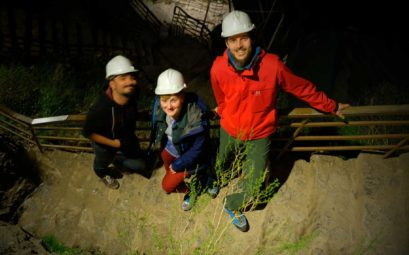 Mustafa, Natalia und Sebastian stehen auf einer Treppe. Alle tragen weiße Schutzhelme.