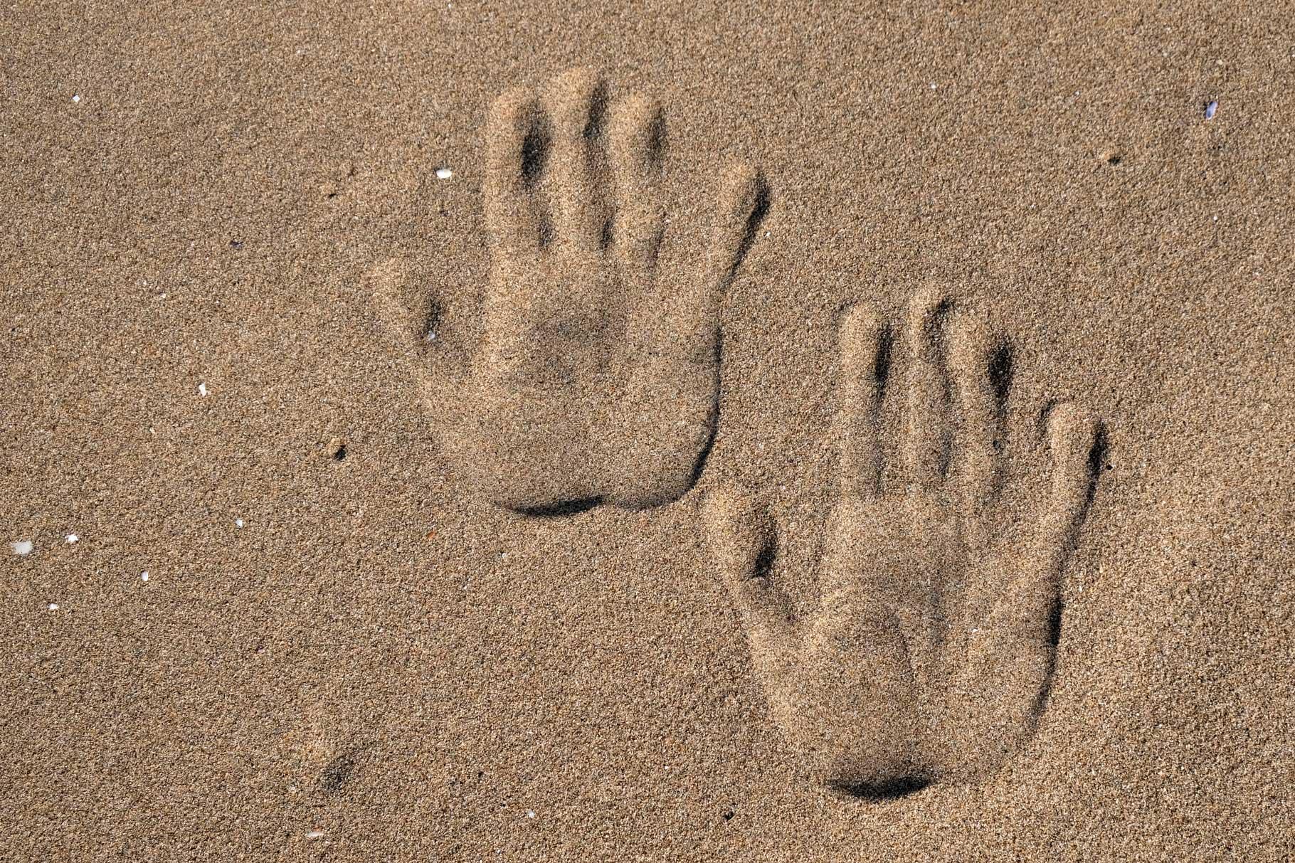 Zwei Handabdrücke im Sand