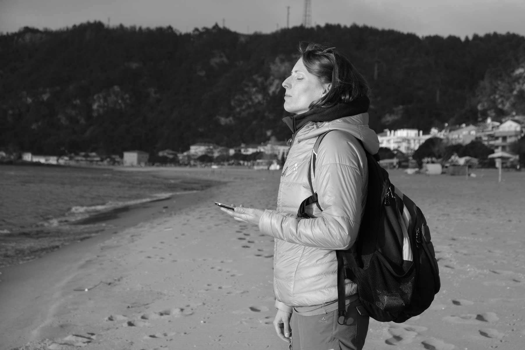 Leo steht mit Handy in der Hand am Strand