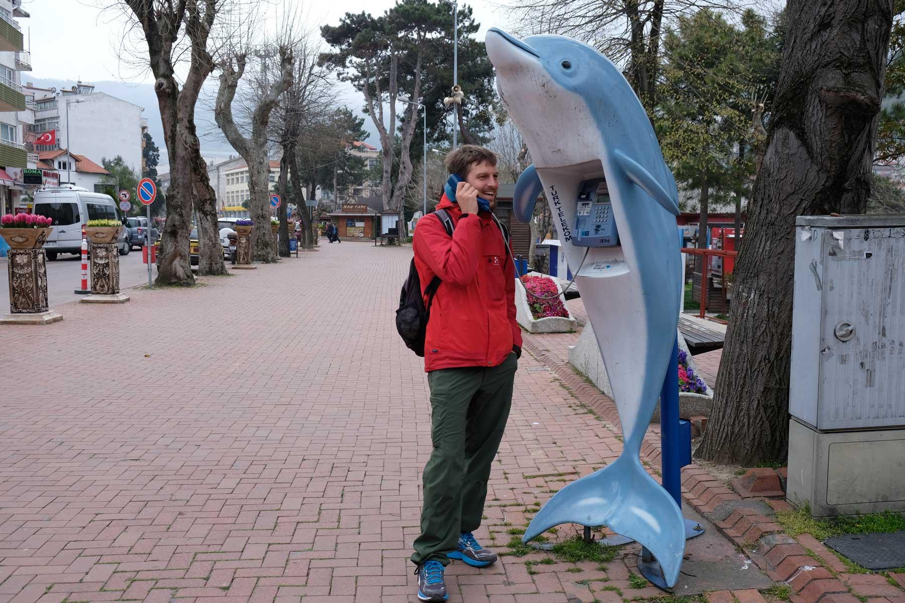 Sebastian telefoniert an einer Telefonzelle in Delfinform