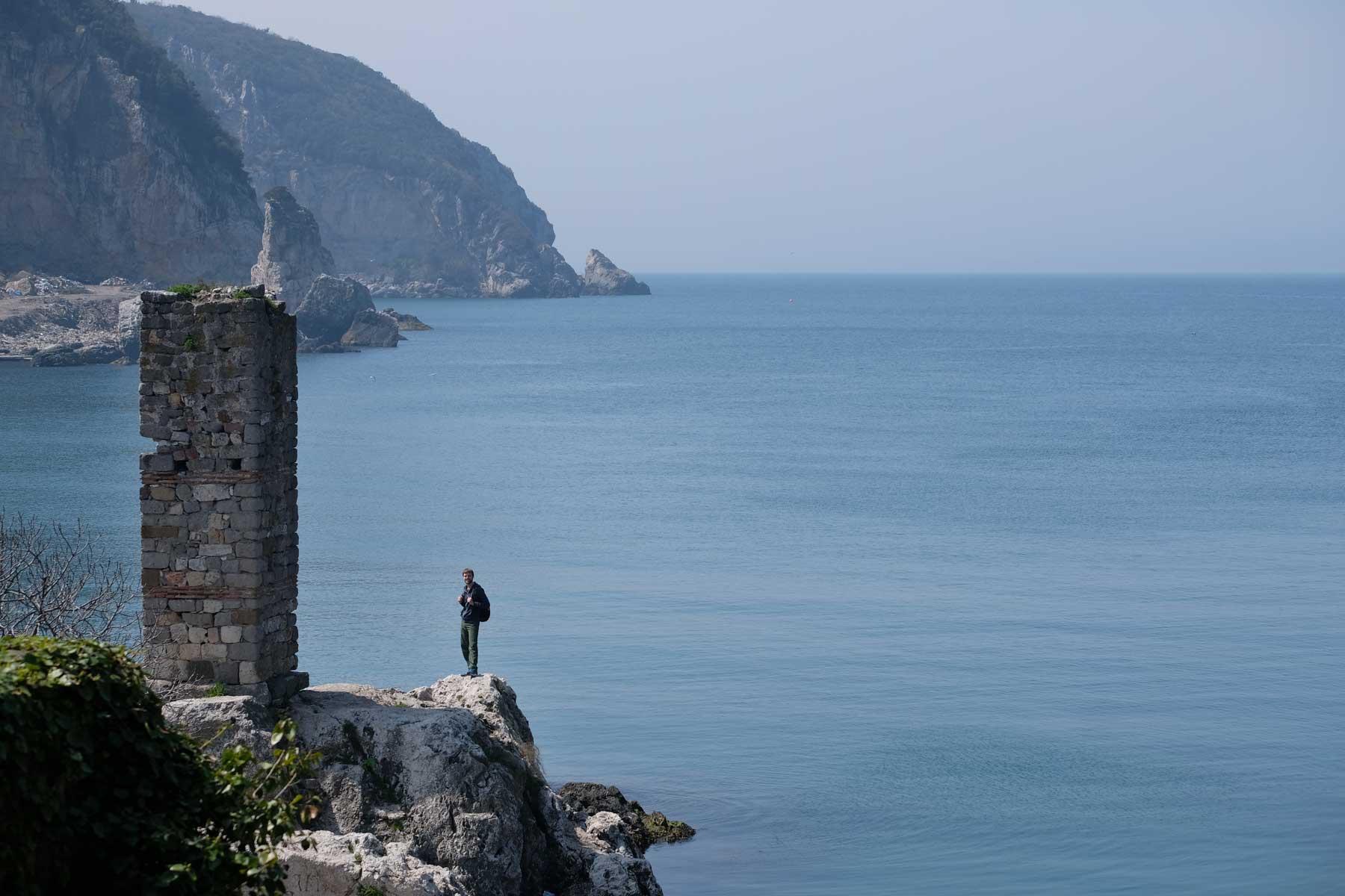 Sebastian neben einem Steinturm am Ufer