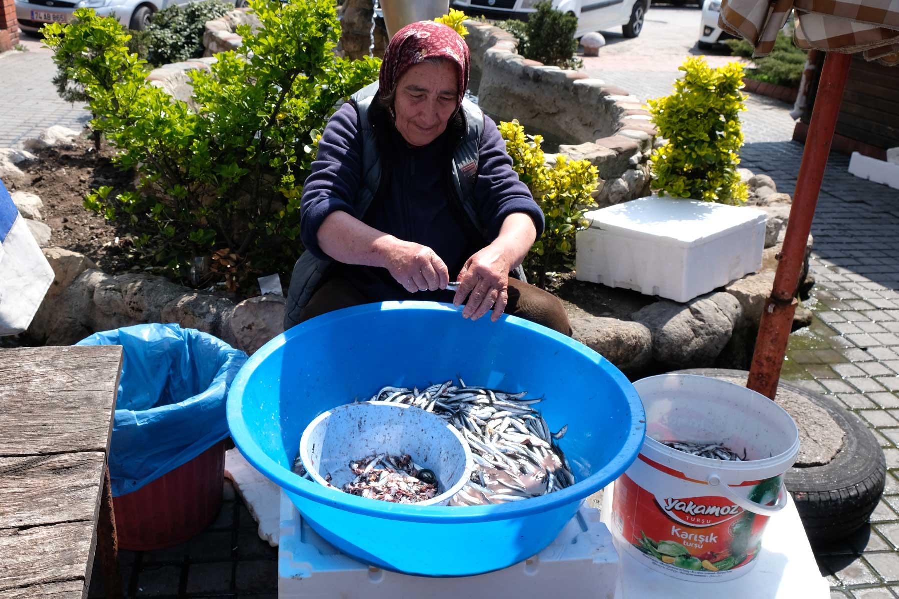 Eine Frau nimmt kleine Fische aus