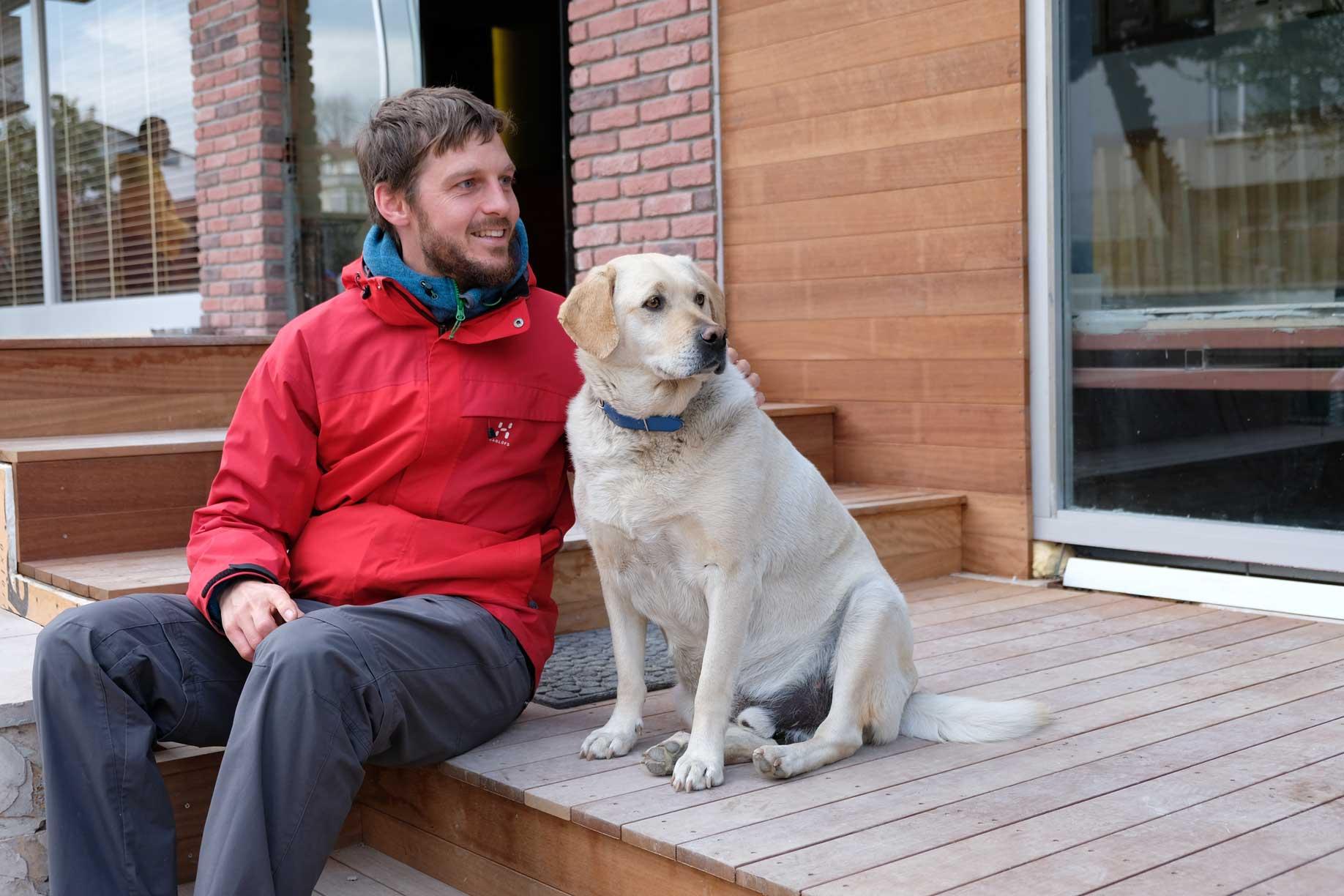 Sebastian sitzt neben einem Hund