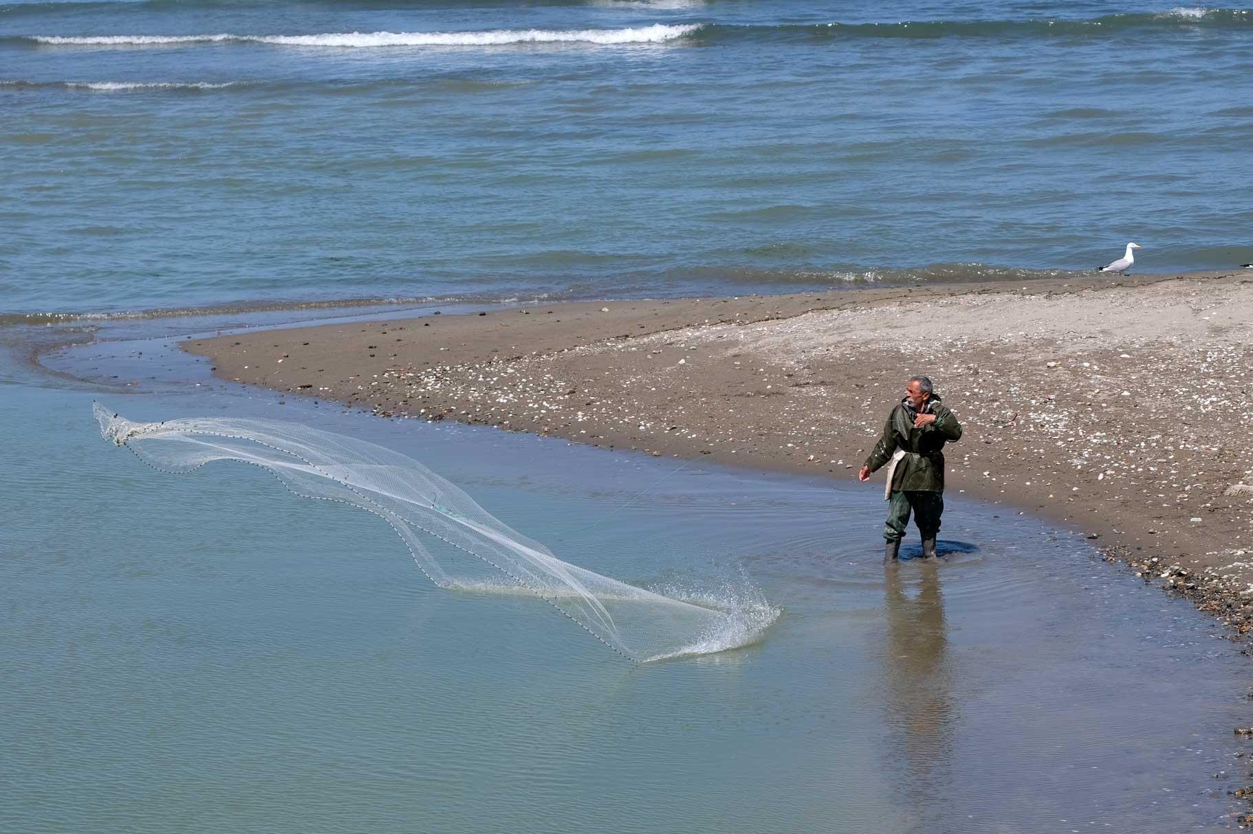 Ein Fischer wirft in Ufernähe ein Netz aus