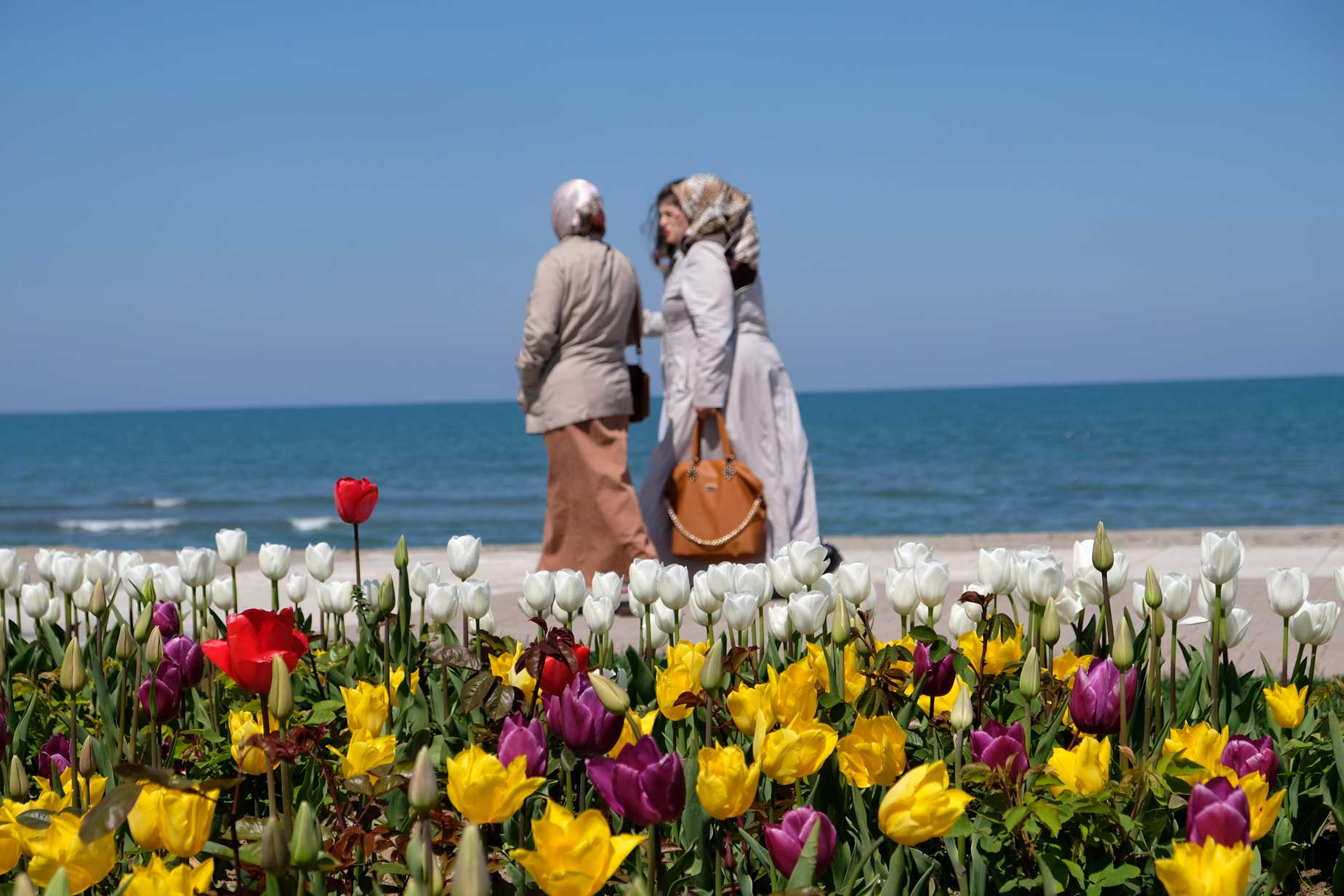 Türkische Frauen spazieren an der Uferpromenade vor einem Tulpenbeet