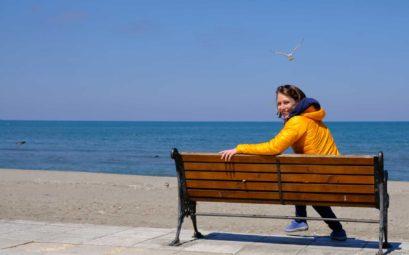 Leo sitzt auf einer Bank am Meer