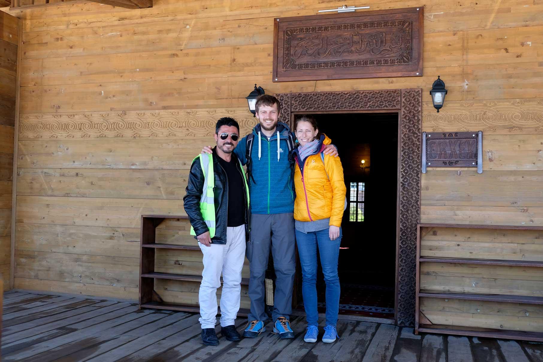 Sebastian und Leo stehen mit einem Mann vor der Holzmoschee