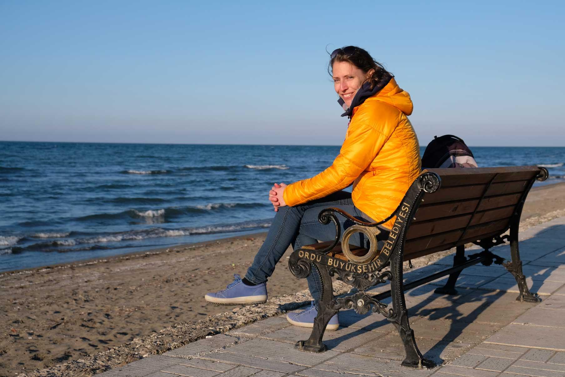 Leo sitzt auf einer Bank am Strand