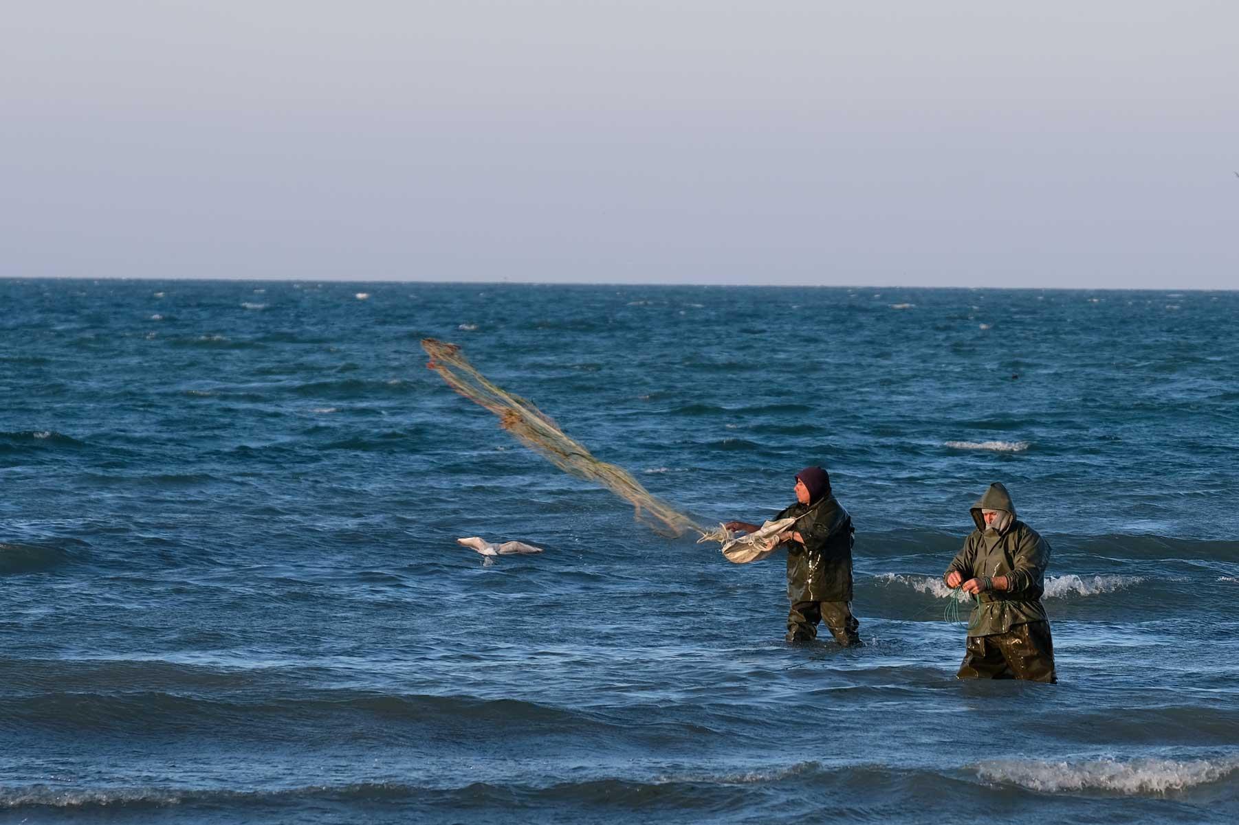 Zwei Fischer werfen im Meer stehend ein Netz aus