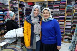 Leo steht neben einer Frau in einem Geschäft. Beide tragen ein Kopftuch.