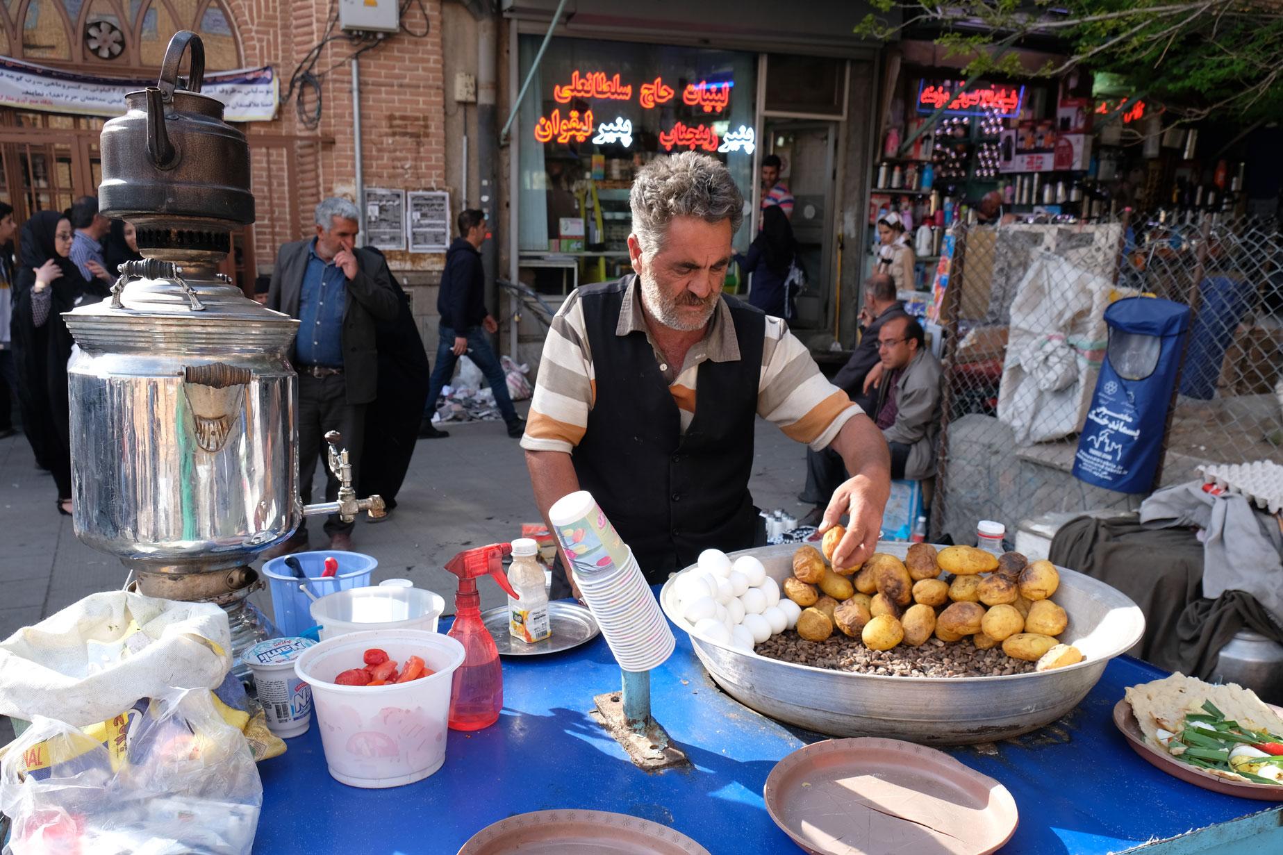 Ein Verkäufer bereitet geröstete Kartoffeln zu