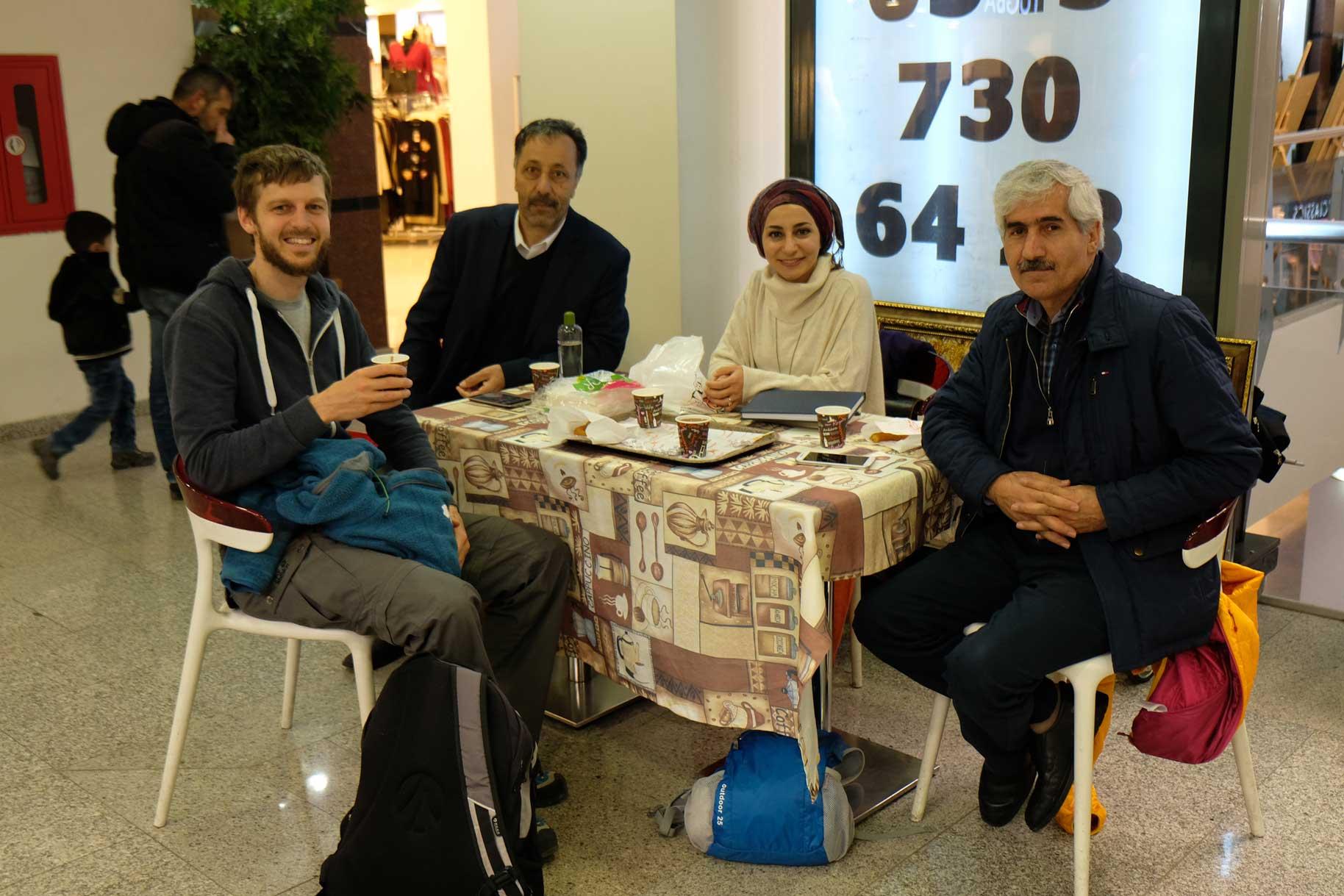 Sebastian und Fesih sitzen mit einem Mann und einer Frau am Tisch und trinken Kaffee