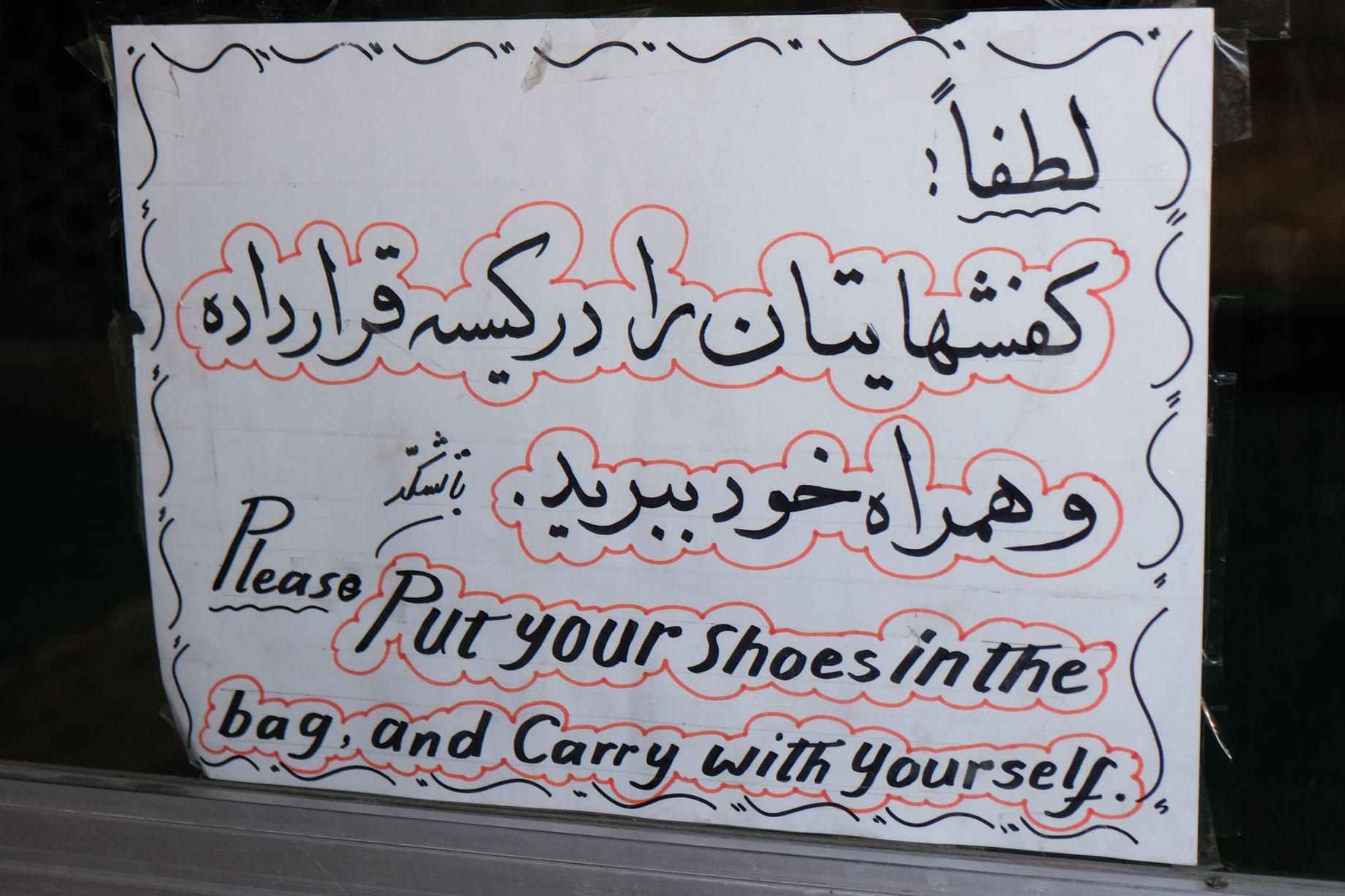 Ein Schild mit der Aufforderung, die Schuhe in eine Tüte zu packen und sie bei sich zu tragen