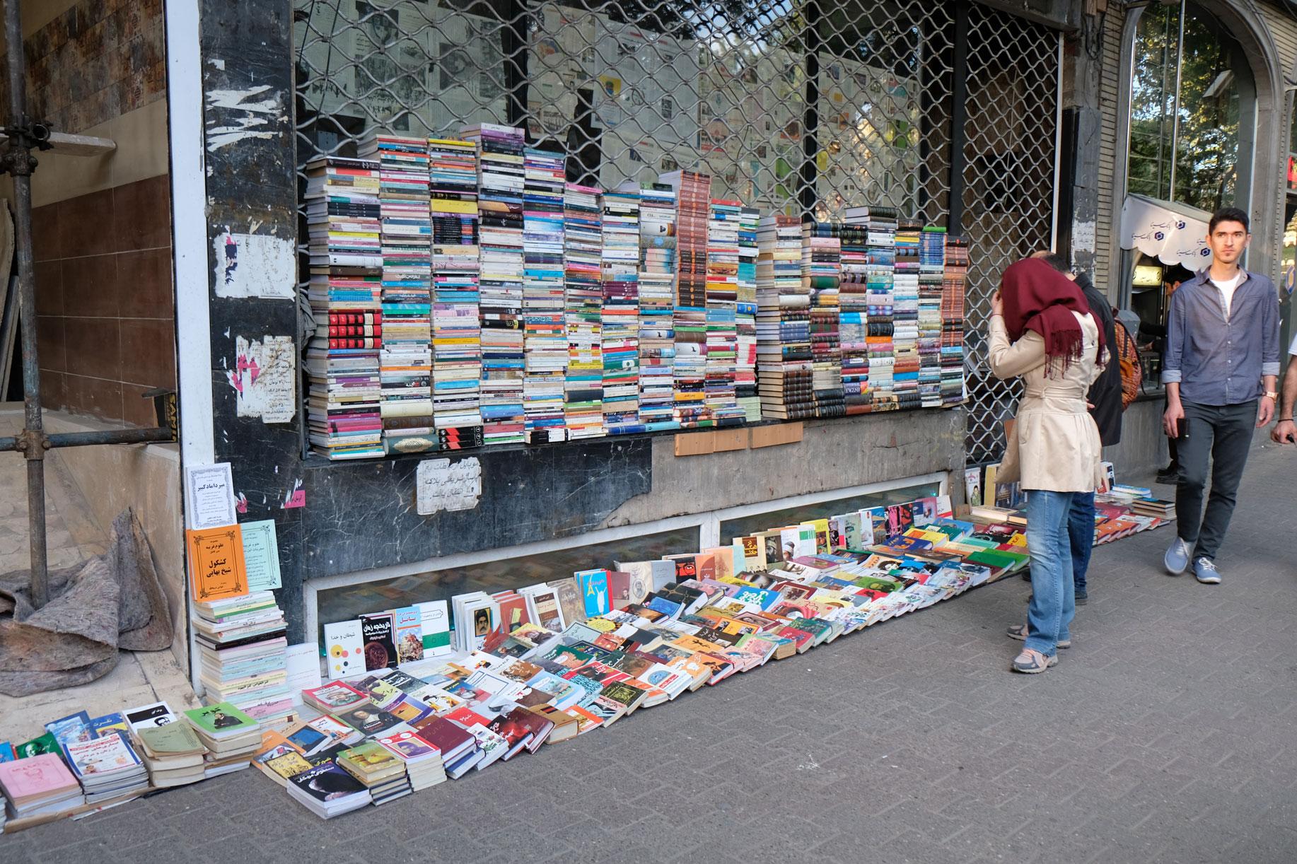 Vor einem geschlossenen Geschäft sind viele Bücher zu Stapeln angeordnet