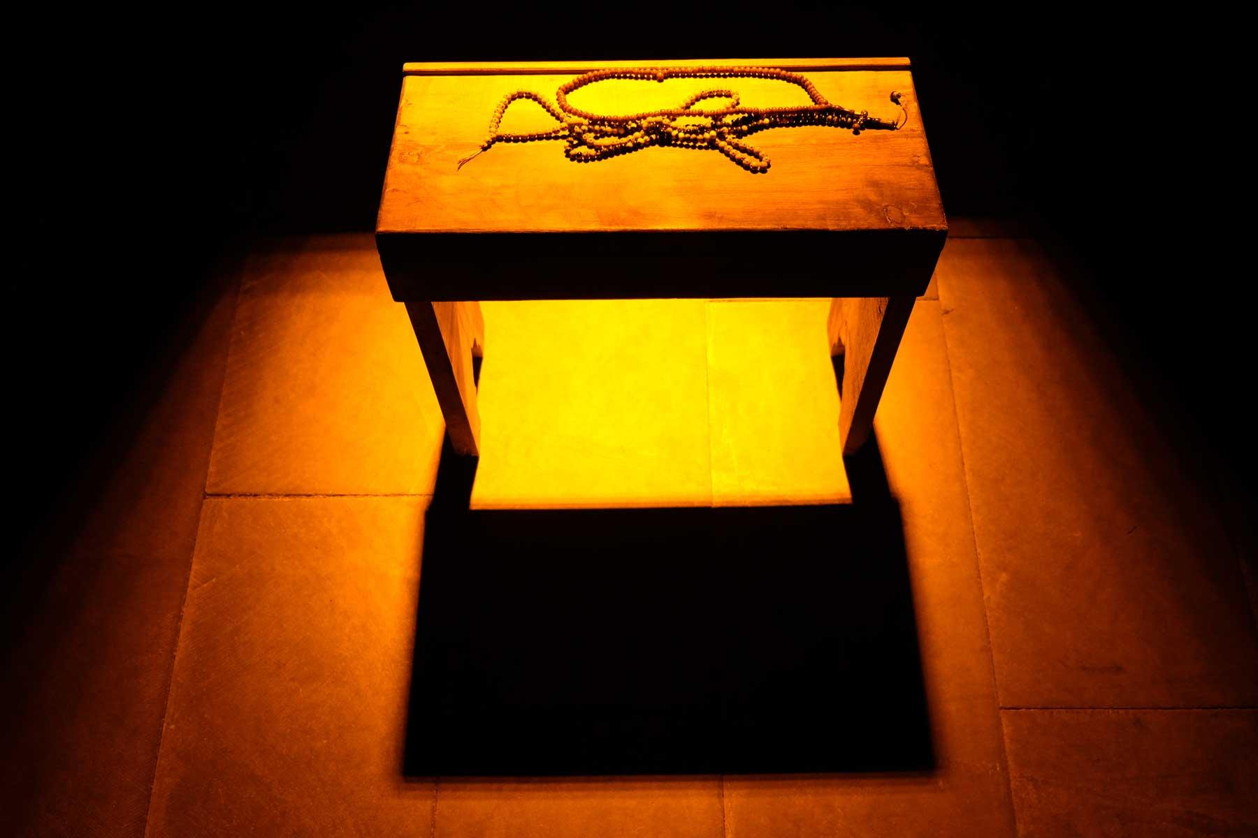 Eine Gebetskette liegt auf einem kleinen Holztisch