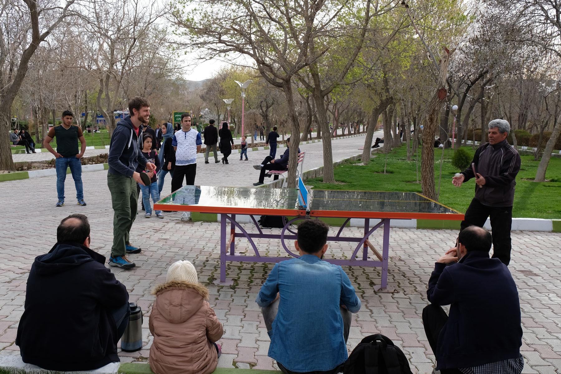 Sebastian spielt im Elgoli-Park mit einem Mann Tischtennis. Einige Leute beobachten das Match.