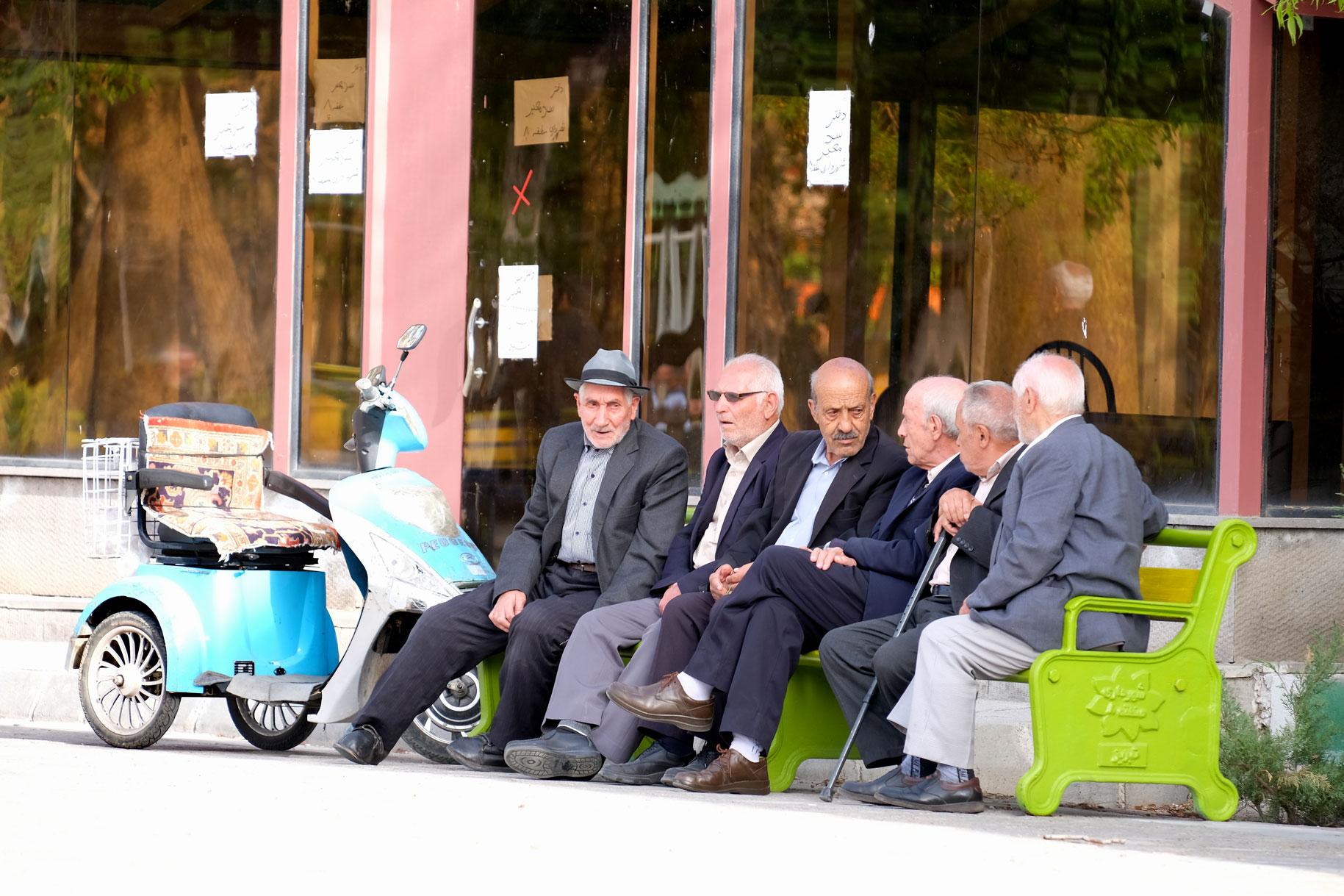 Sechs ältere Männer sitzen auf einer Bank und unterhalten sich