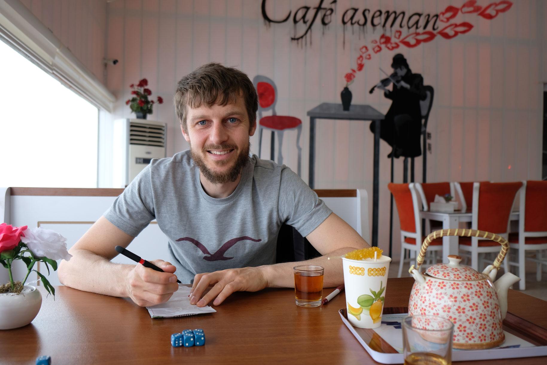 Sebastian sitzt mit Spielwürfeln und einer Tasse Tee an einem Tisch