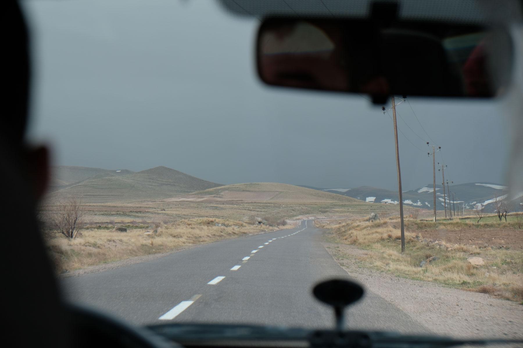 Blick aus dem Auto auf eine Straße und schwarze Regenwolken