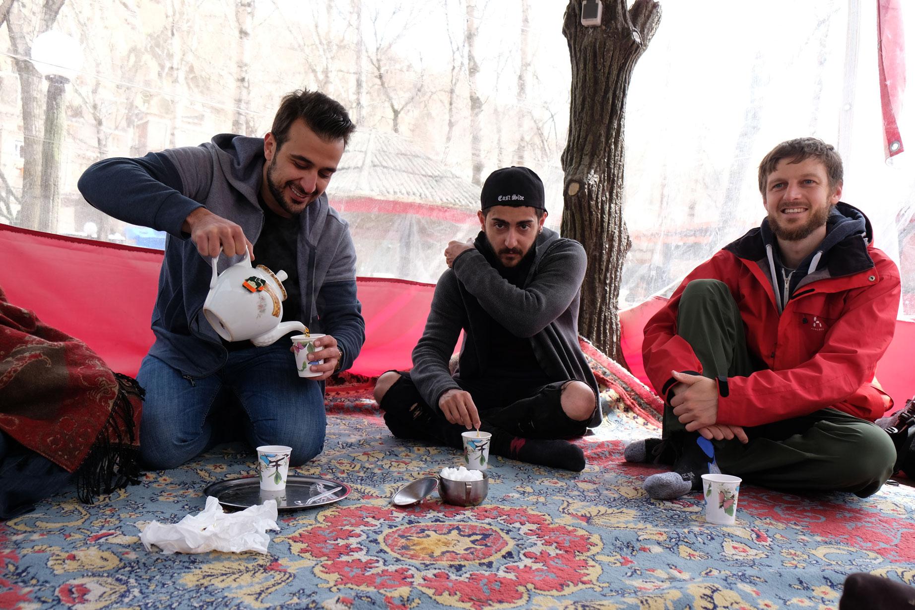 Mahbod, Aryan und Sebastian sitzen auf dem Boden und trinken Tee