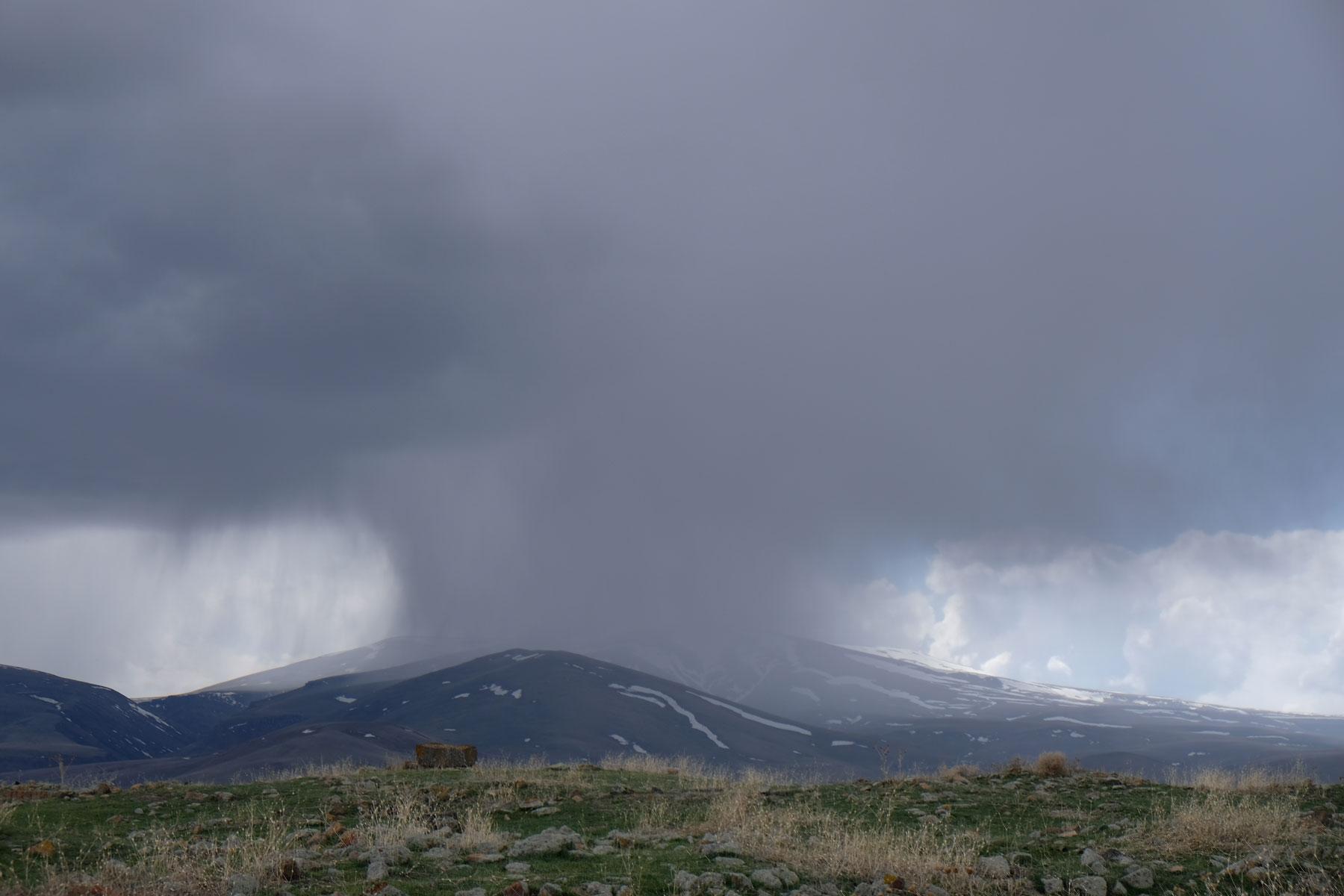 Dunkle Regenwolken und Schauer über einem Berg