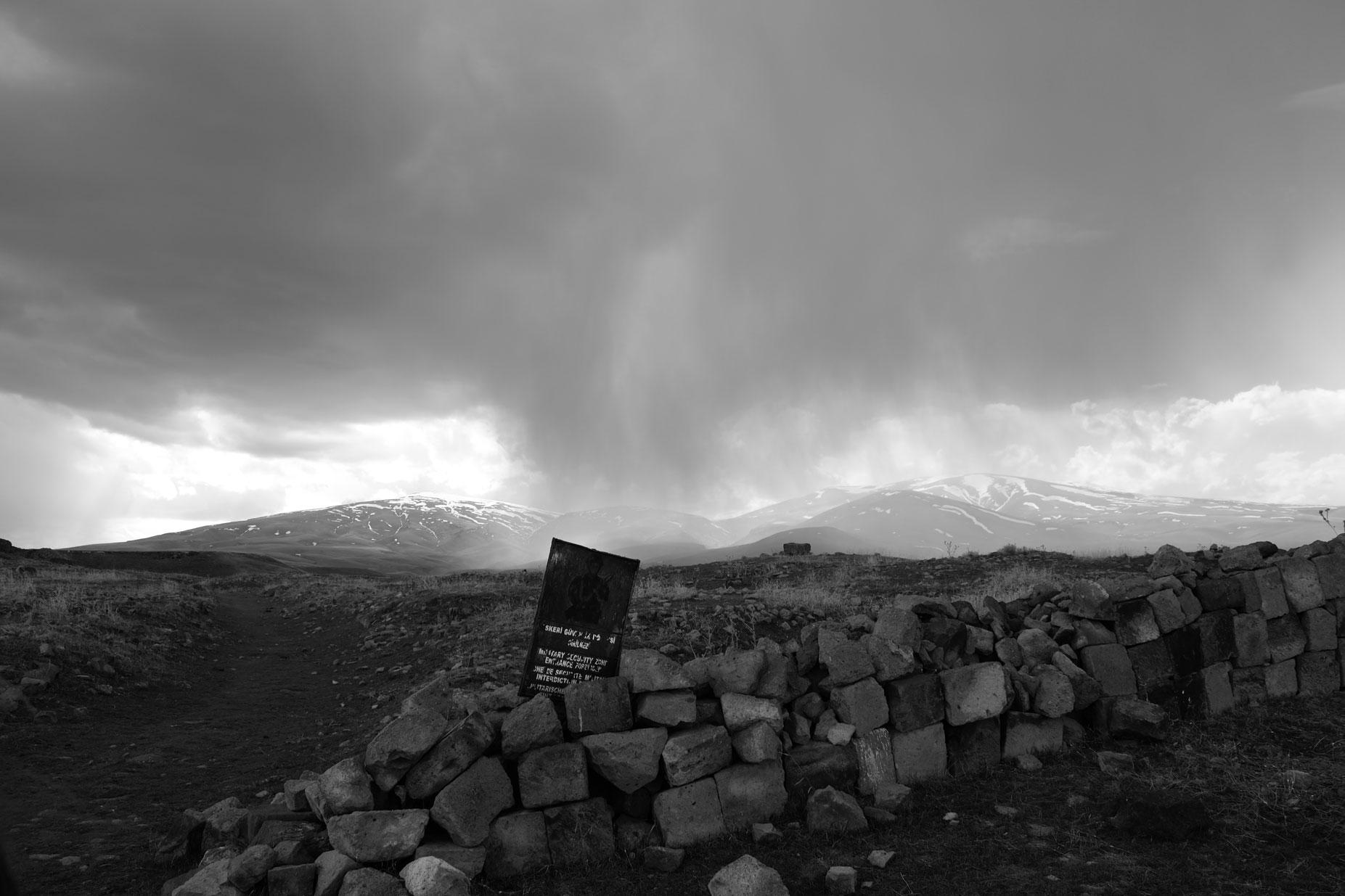 Unwetterartige Regenwolken hinter einer Steinmauer