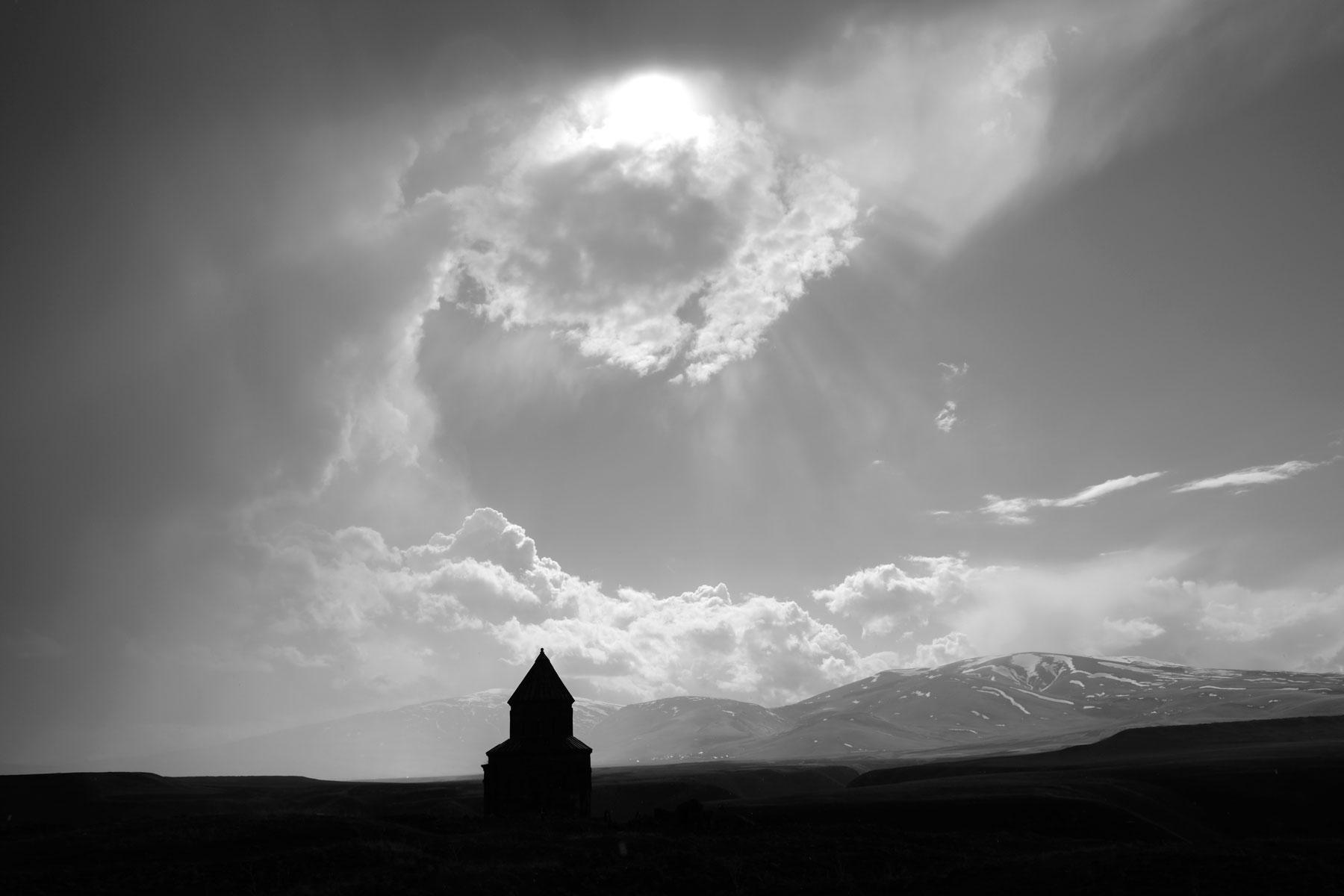 Silhouette des Schamatun der Apostelkirche. Die Sonne kommt hinter den Wolken hervor.