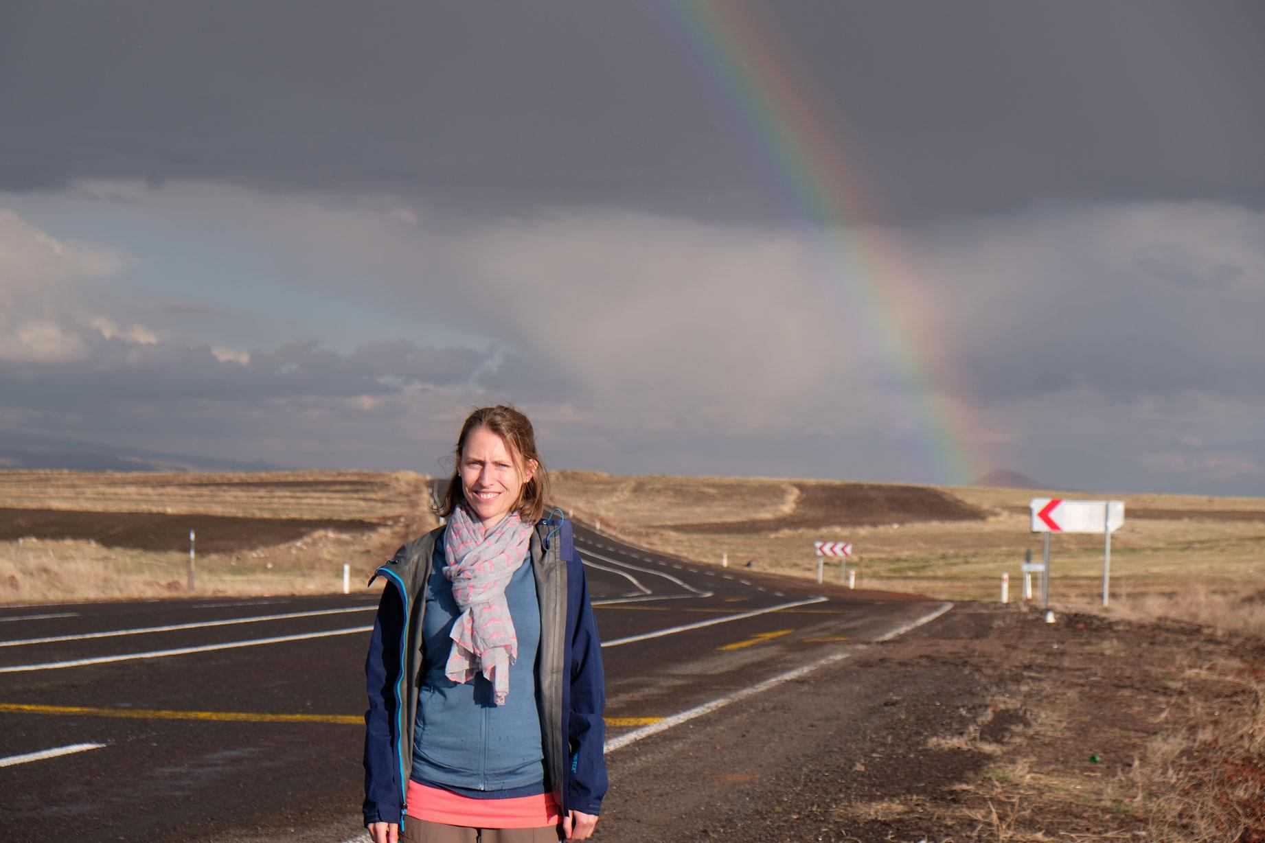 Leo steht auf einer Straße vor einem Regenbogen