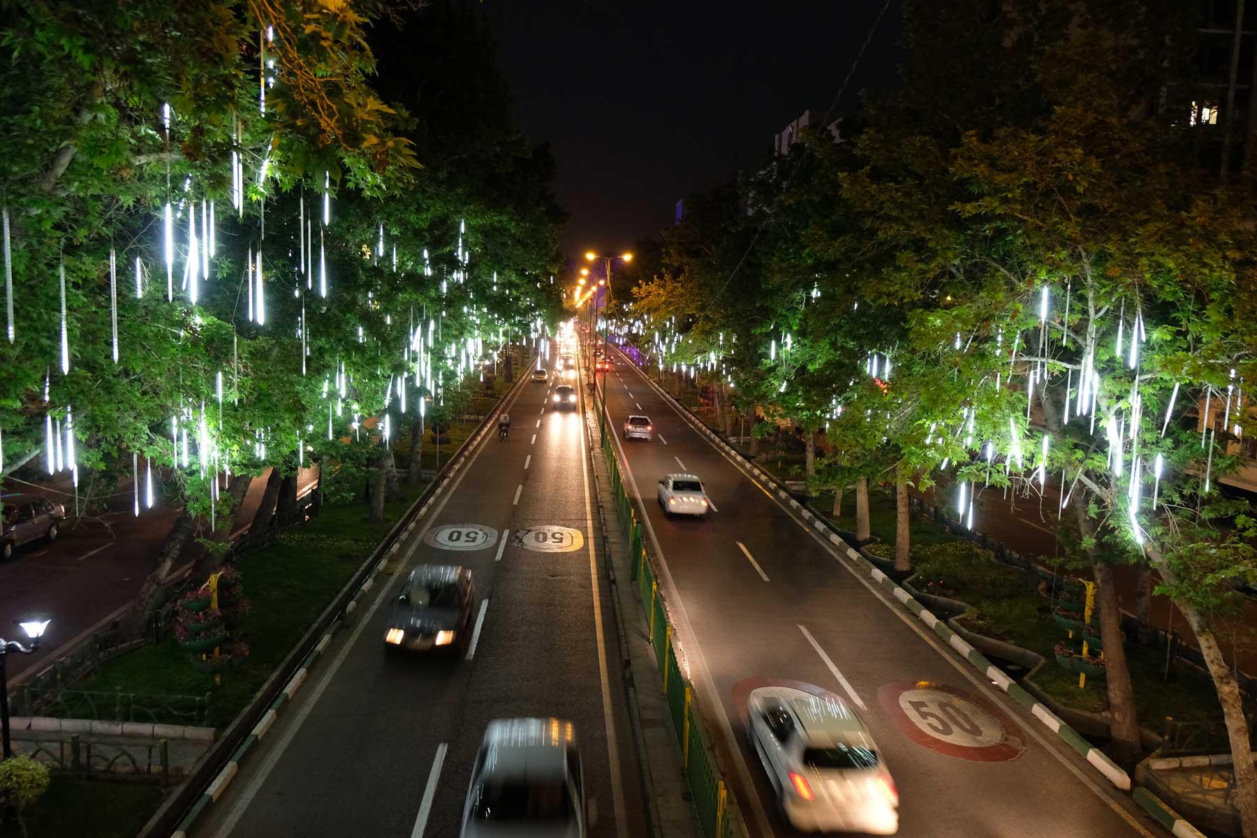 Schnellstraße, die durch beleuchtete Bäume gesäumt ist