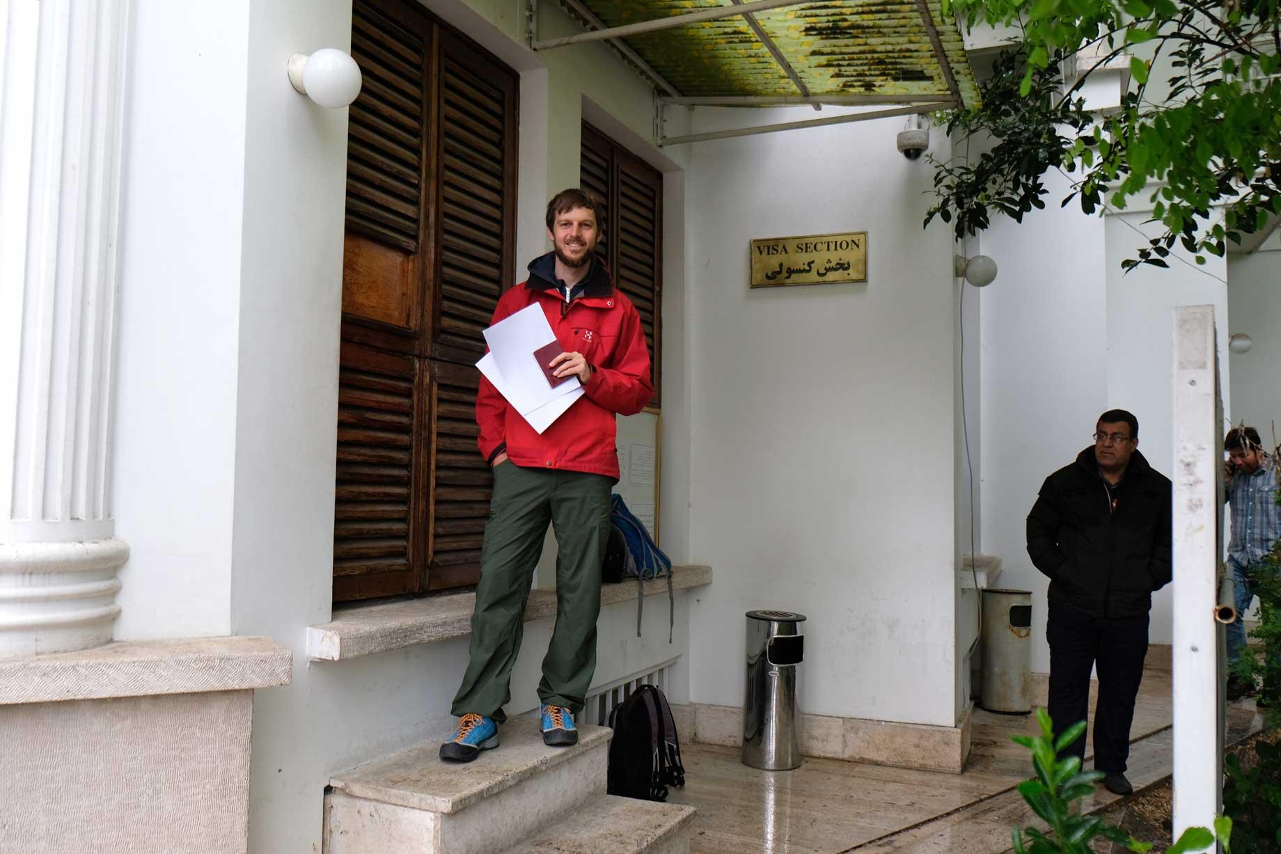 """Sebastian steht mit Pass und Papieren in der Hand vor einem weißen Gebäude mit einem Schild, auf dem """"Visa section"""" steht"""