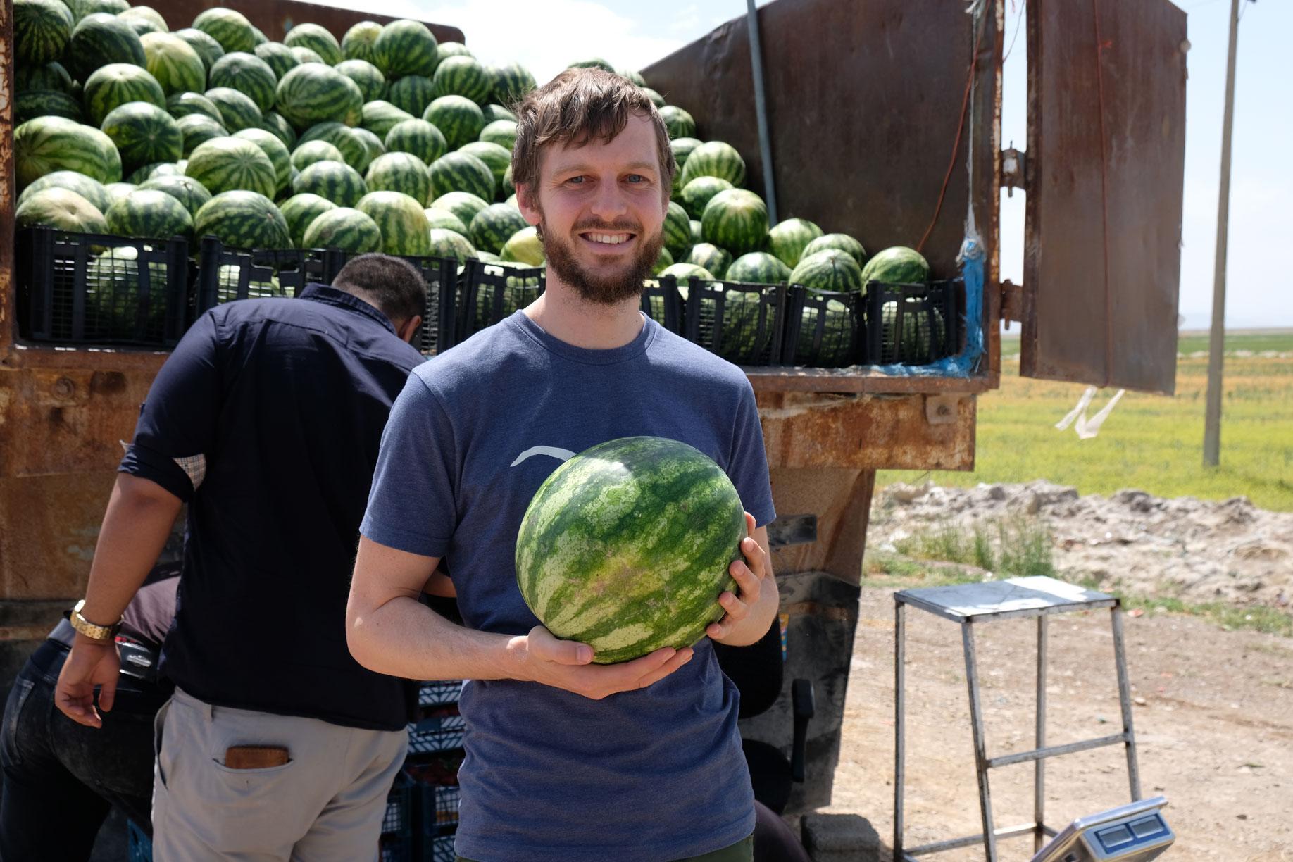 Sebastian hält vor einem Lastwagen, der mit Wassermelonen beladen ist, eine Wassermelone in der Hand