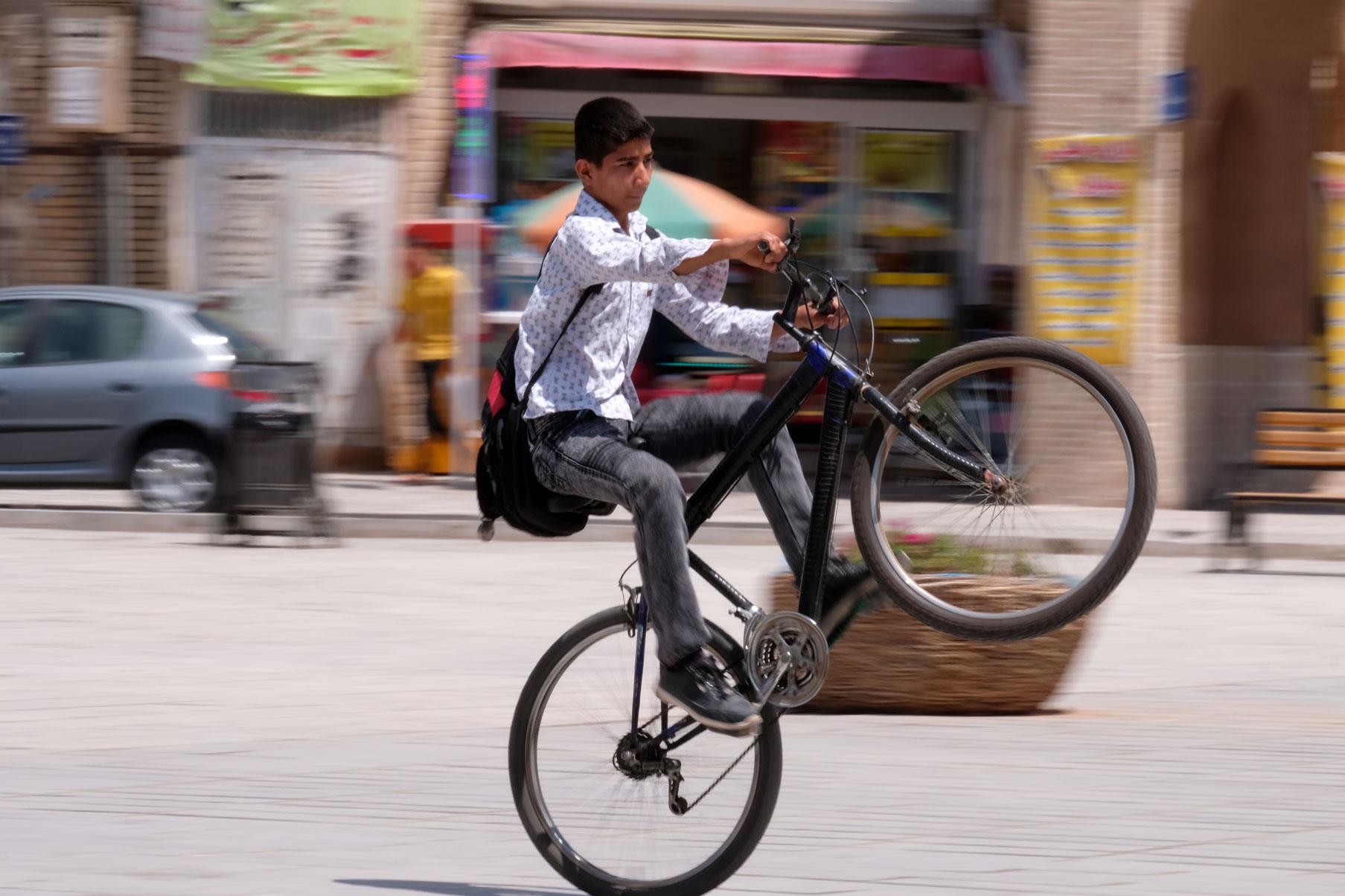 Davor zeigt ein Junge sein Können beim Wheely