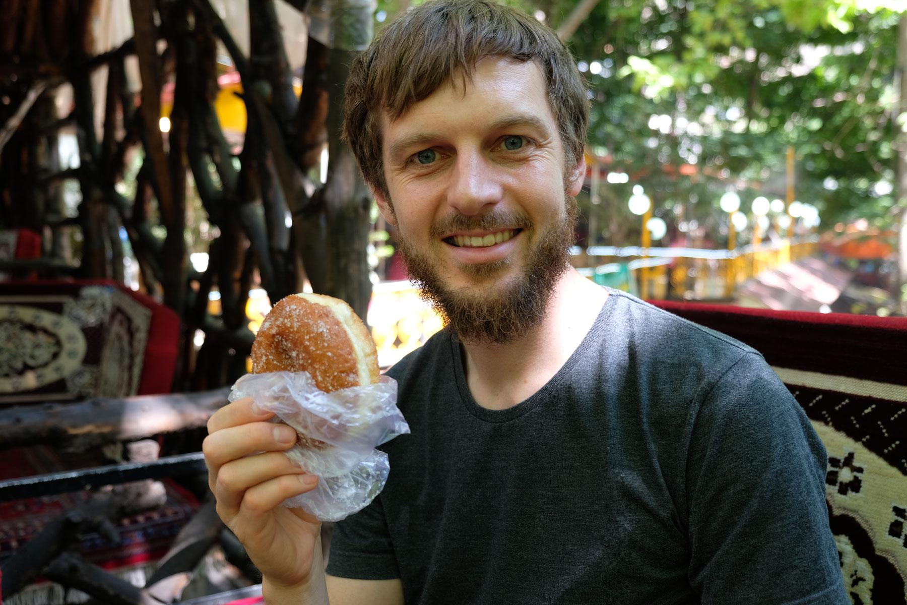 Sebastian hält einen Donut in der Hand