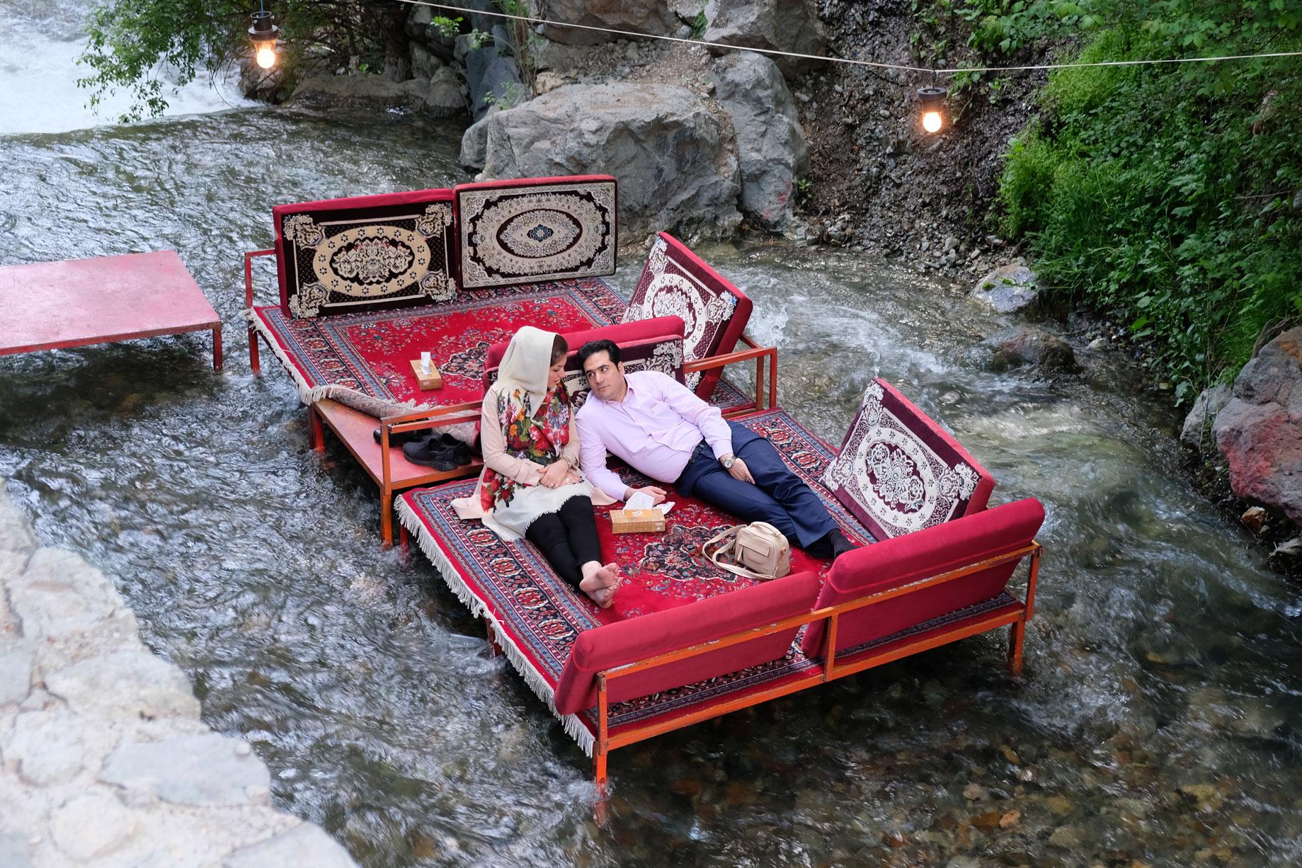 Ein Liebespaar liegt auf einem Bett, das in einem Fluss steht