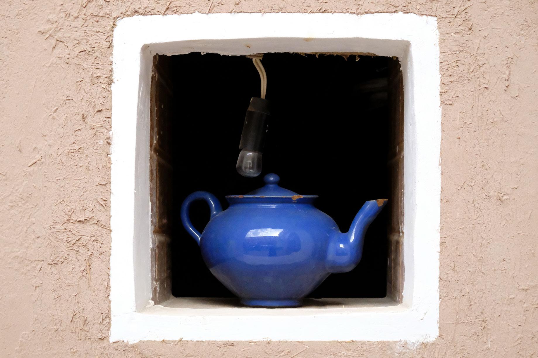 Eine blaue Teekanne in einem kleinen Fenster
