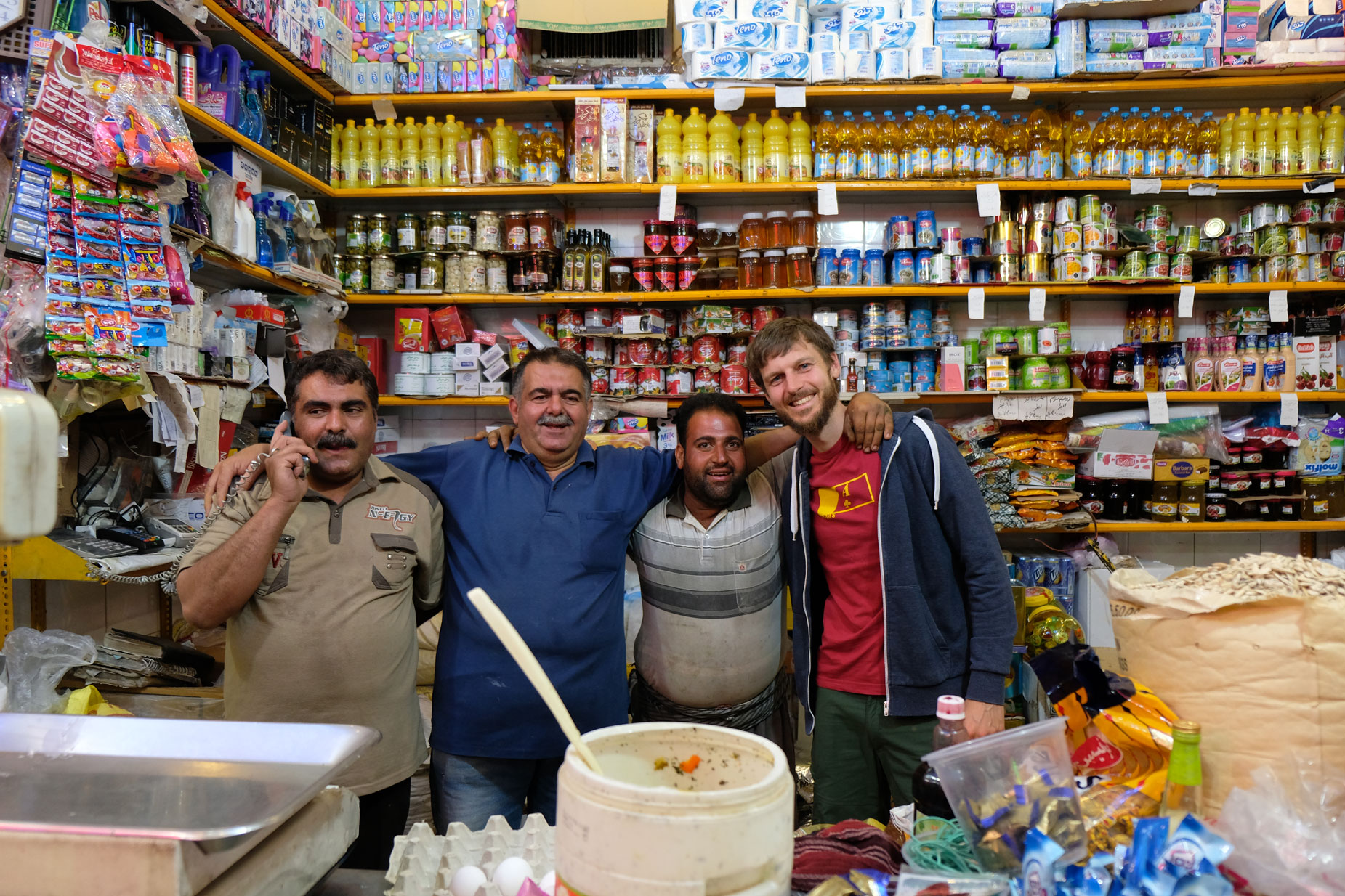 Sebastian mit drei Männern in einem kleinen Lebensmittelgeschäft