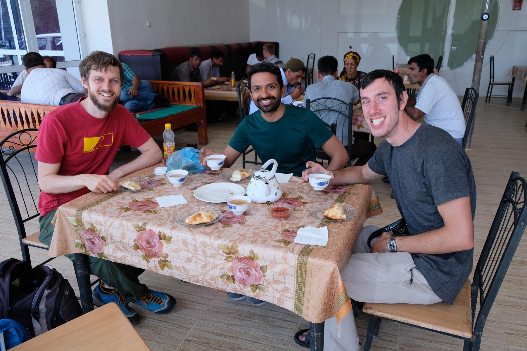Sebastian sitzt mit Yogesh und Nicolas am Tisch und trinkt Tee