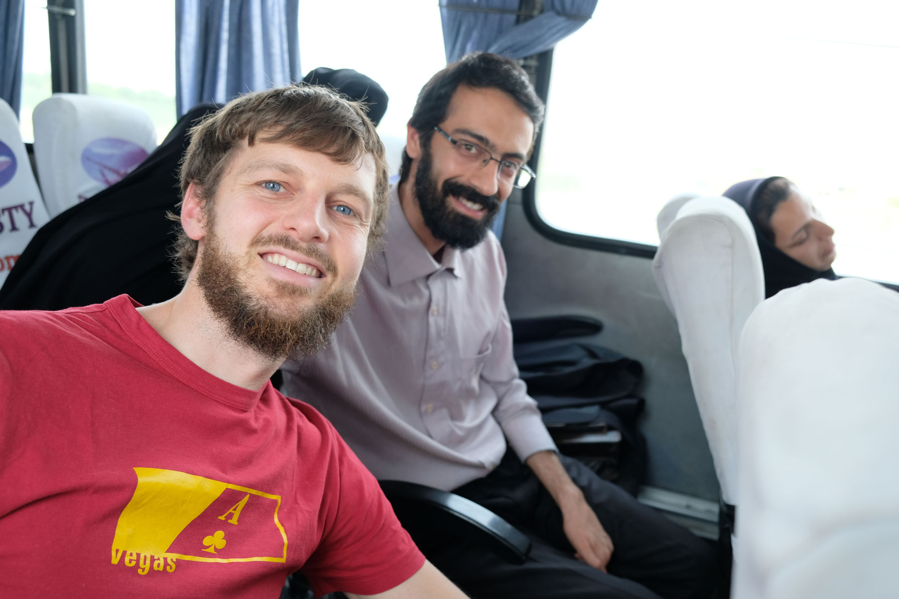Sebastian neben einem Mann imn Bus