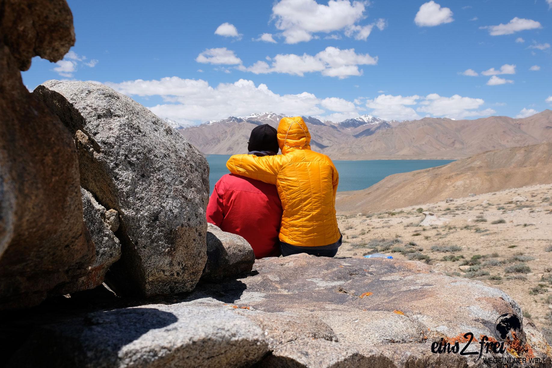 Leo umarmt Sebastian. Sie blicken auf den Yesikul See im Pamirgebirge.