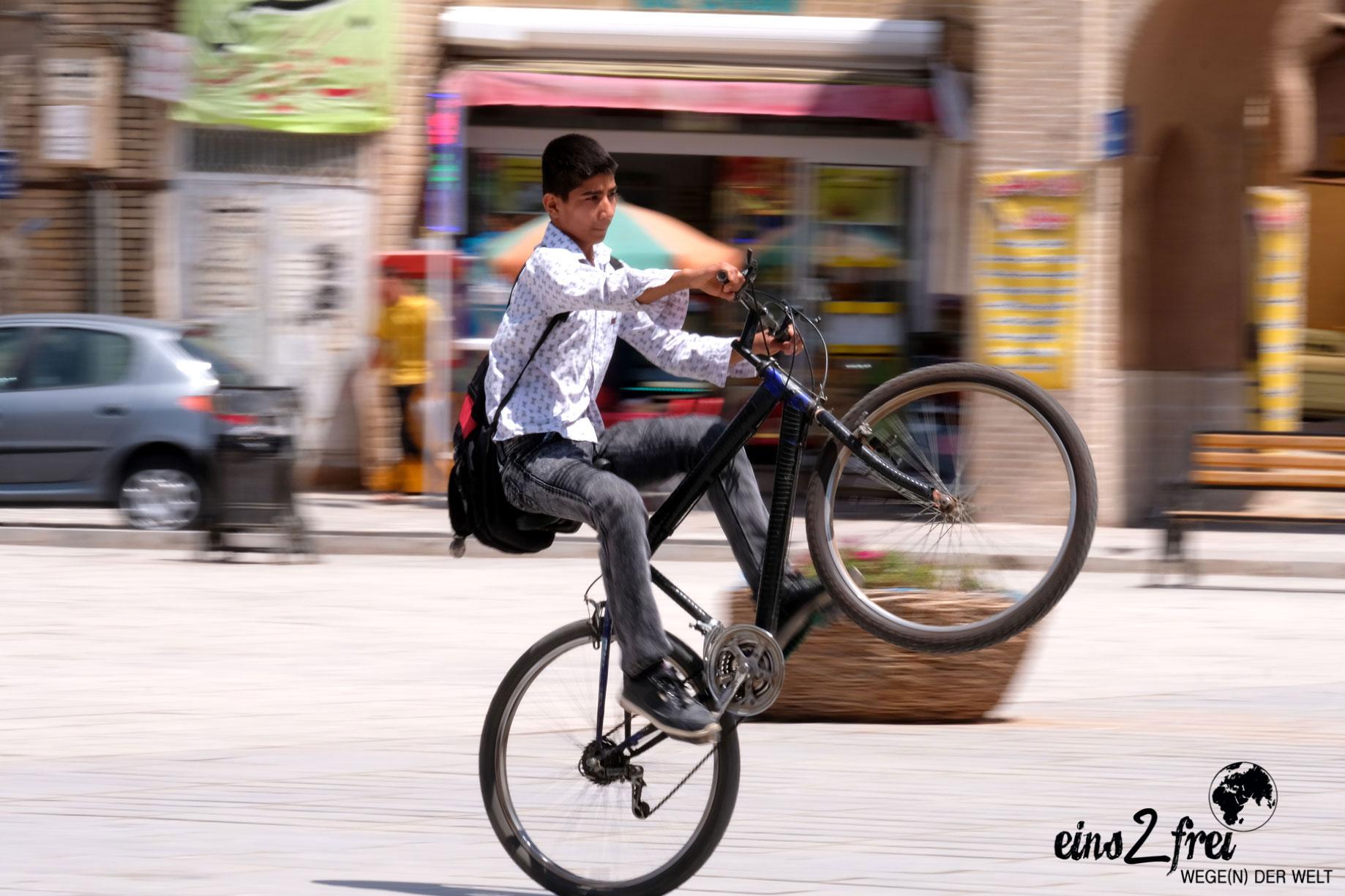 Ein Junge macht mit seinem Fahrrad einen Wheelie