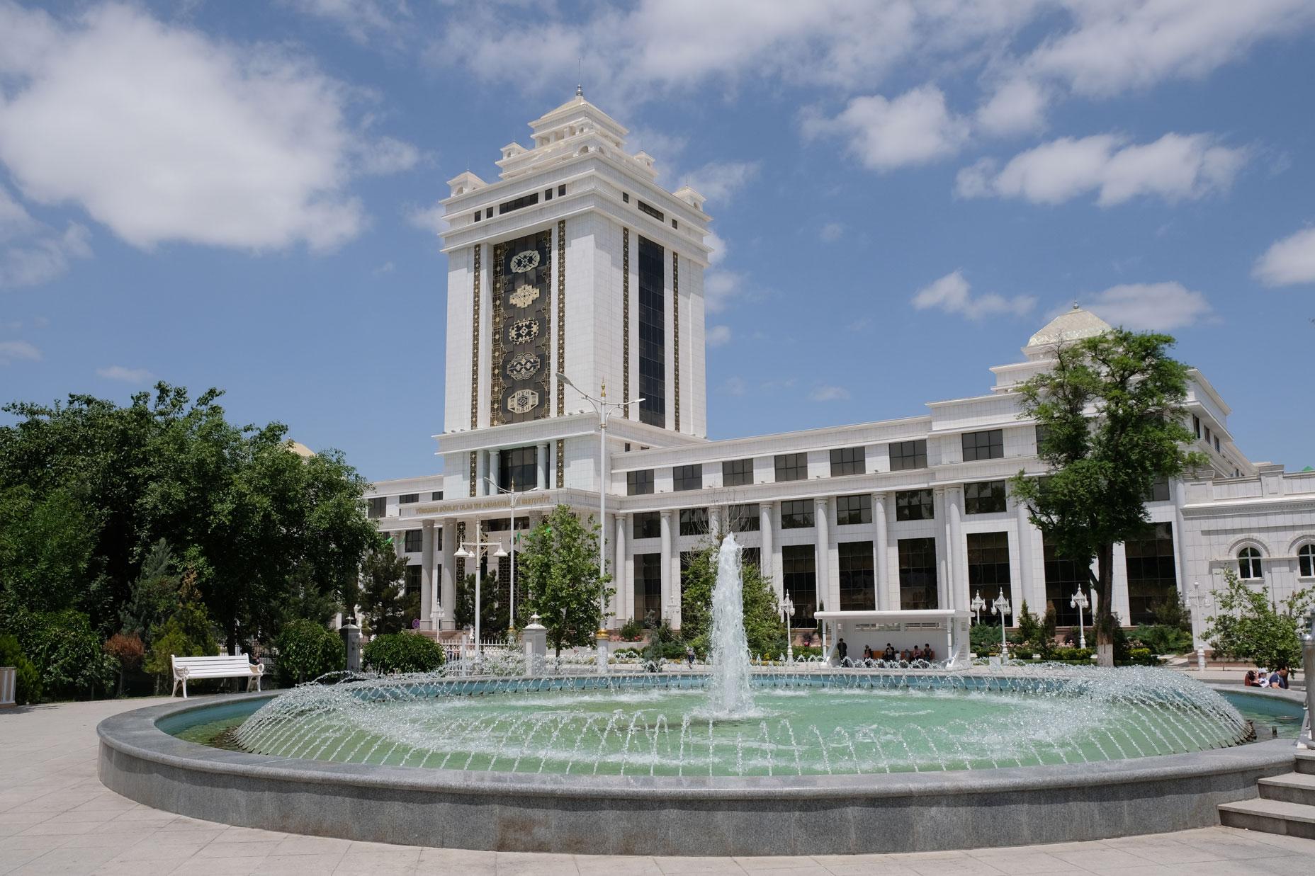 Ein Springbrunnen vor einem mit Marmor verkleideten Gebäude in Aşgabat