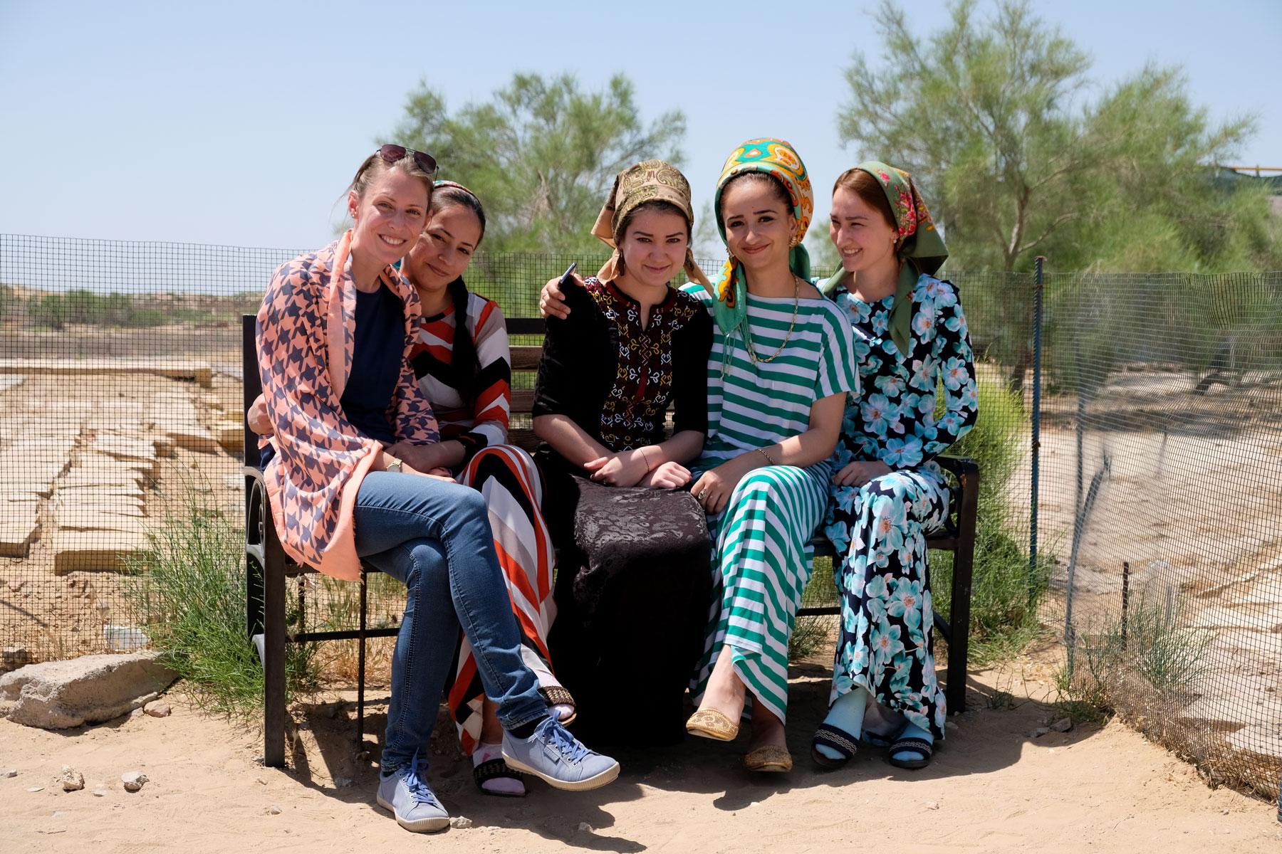 Leo sitzt auf einer Bank neben drei bunt gekleideten Frauen