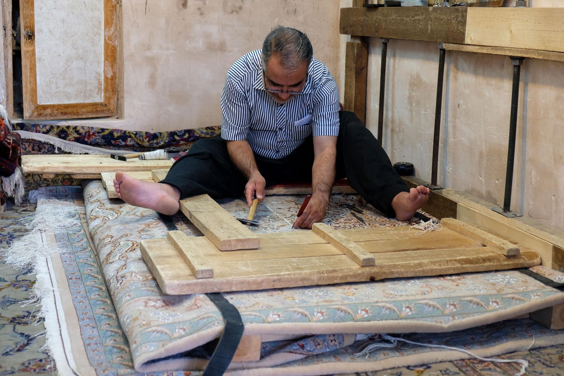 Ein Mann repariert einen Teppich