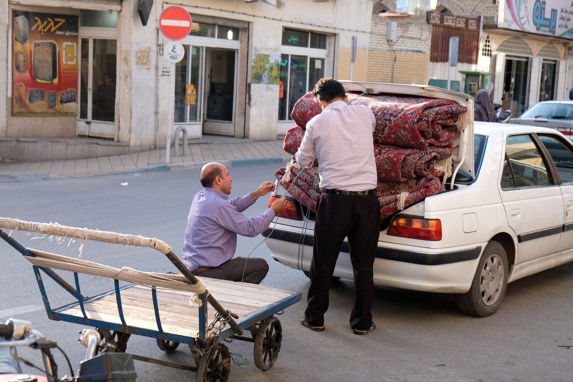 Zwei Männer binden drei große Teppiche am Kofferaum eines Autos fest