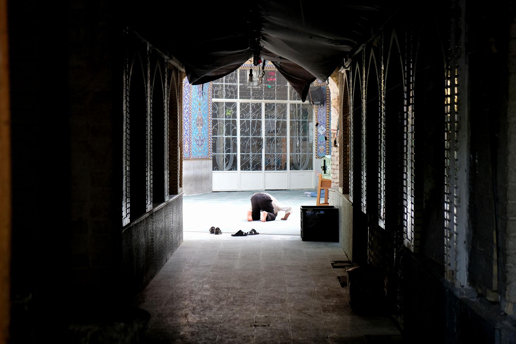 Ein Mann kniet zum Gebet