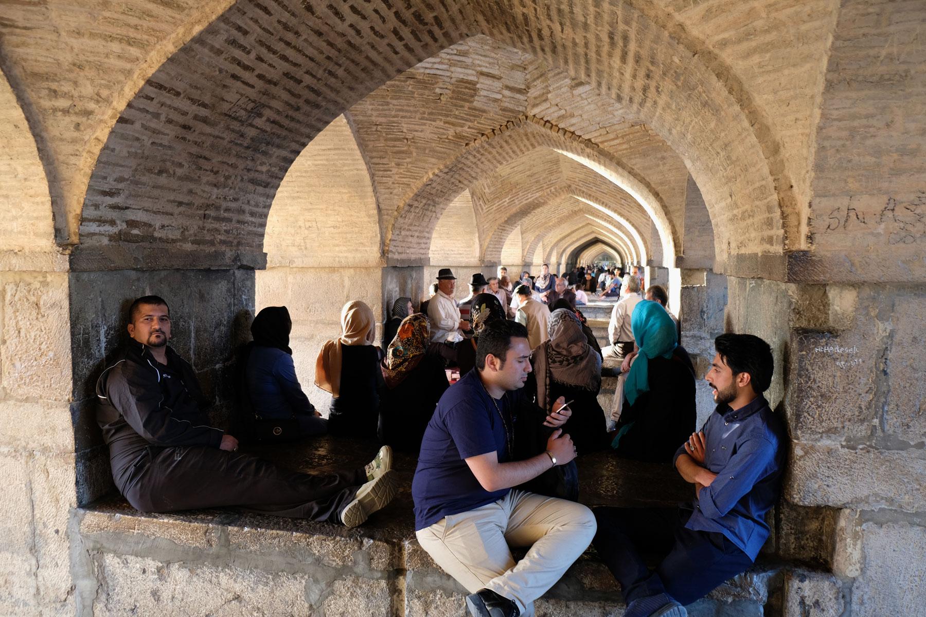 Menschen sitzen unter Torbögen unter einer Brücke