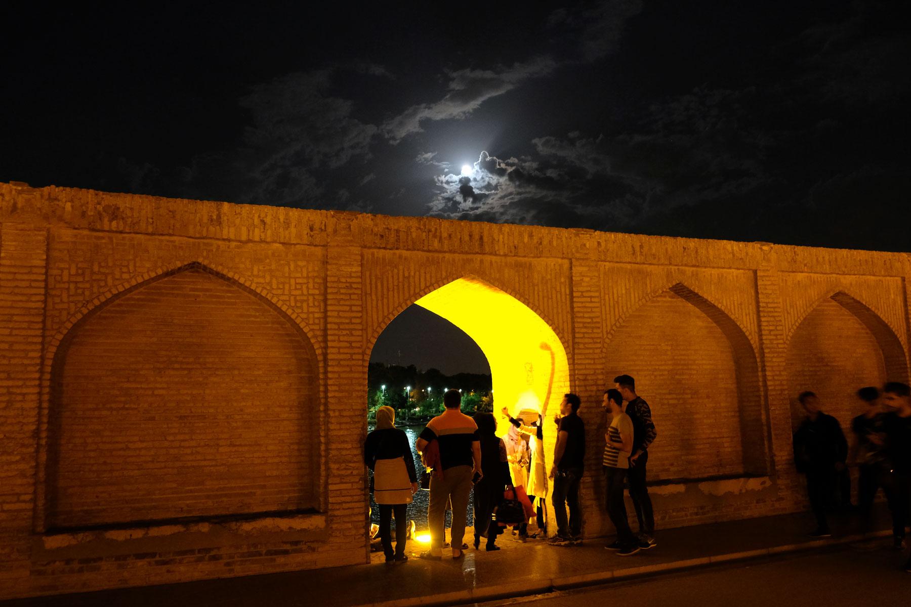 Menschen stehen im Abendlicht in einem Torbogen eine Mauer